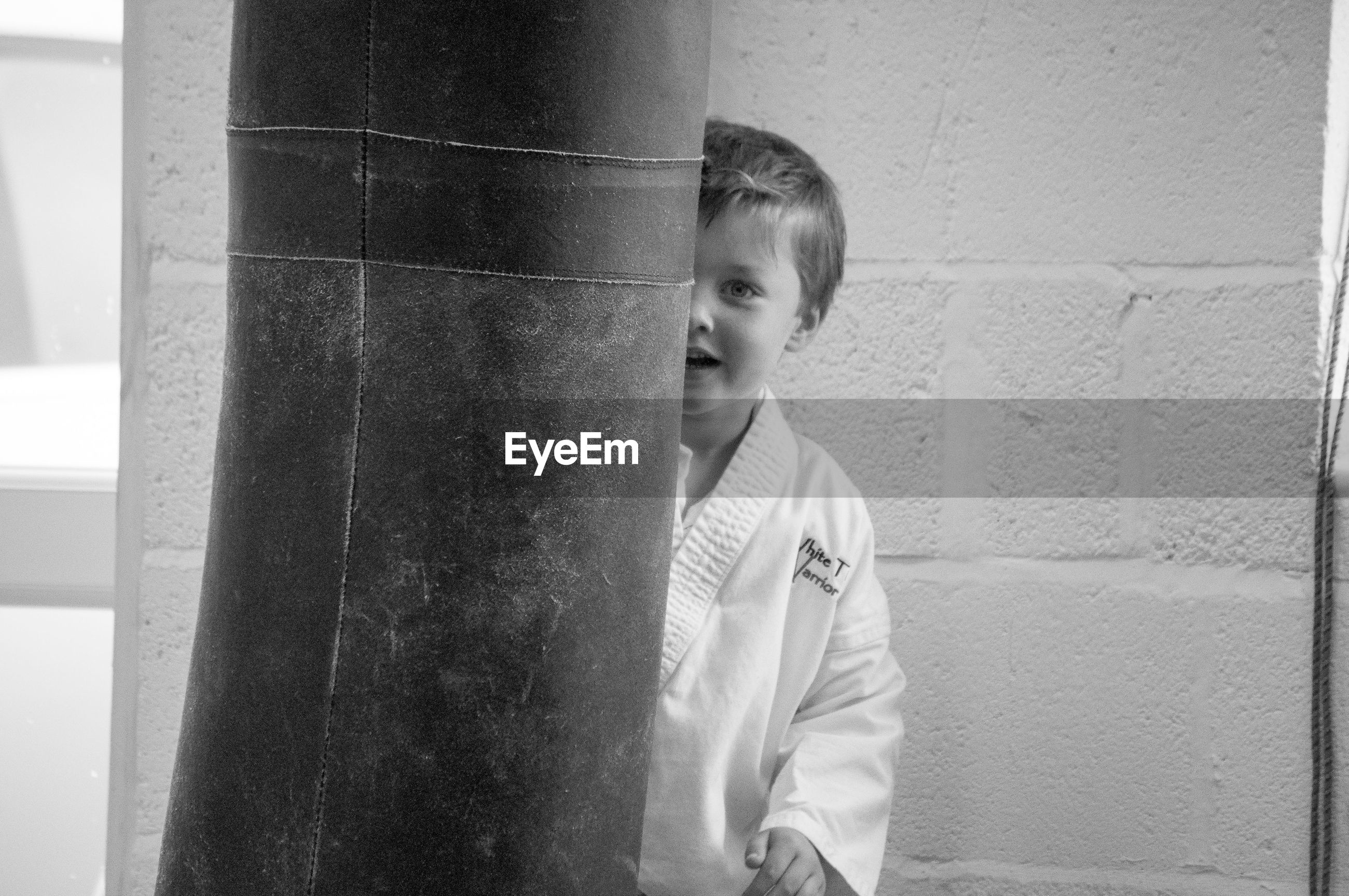 Portrait of boy in sport clothing behind punching bag at martial arts classroom