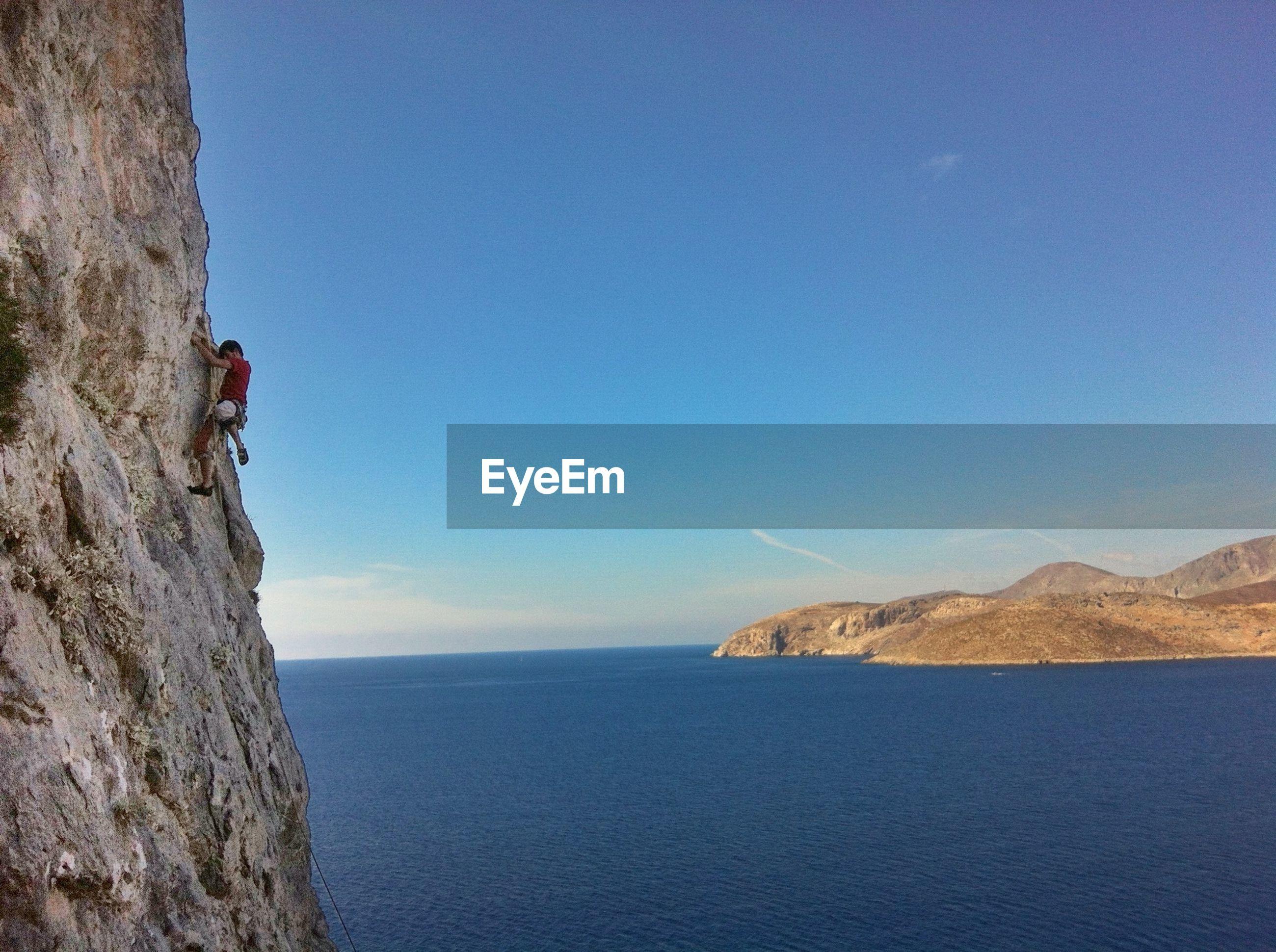 Man climbing rock against calm sea