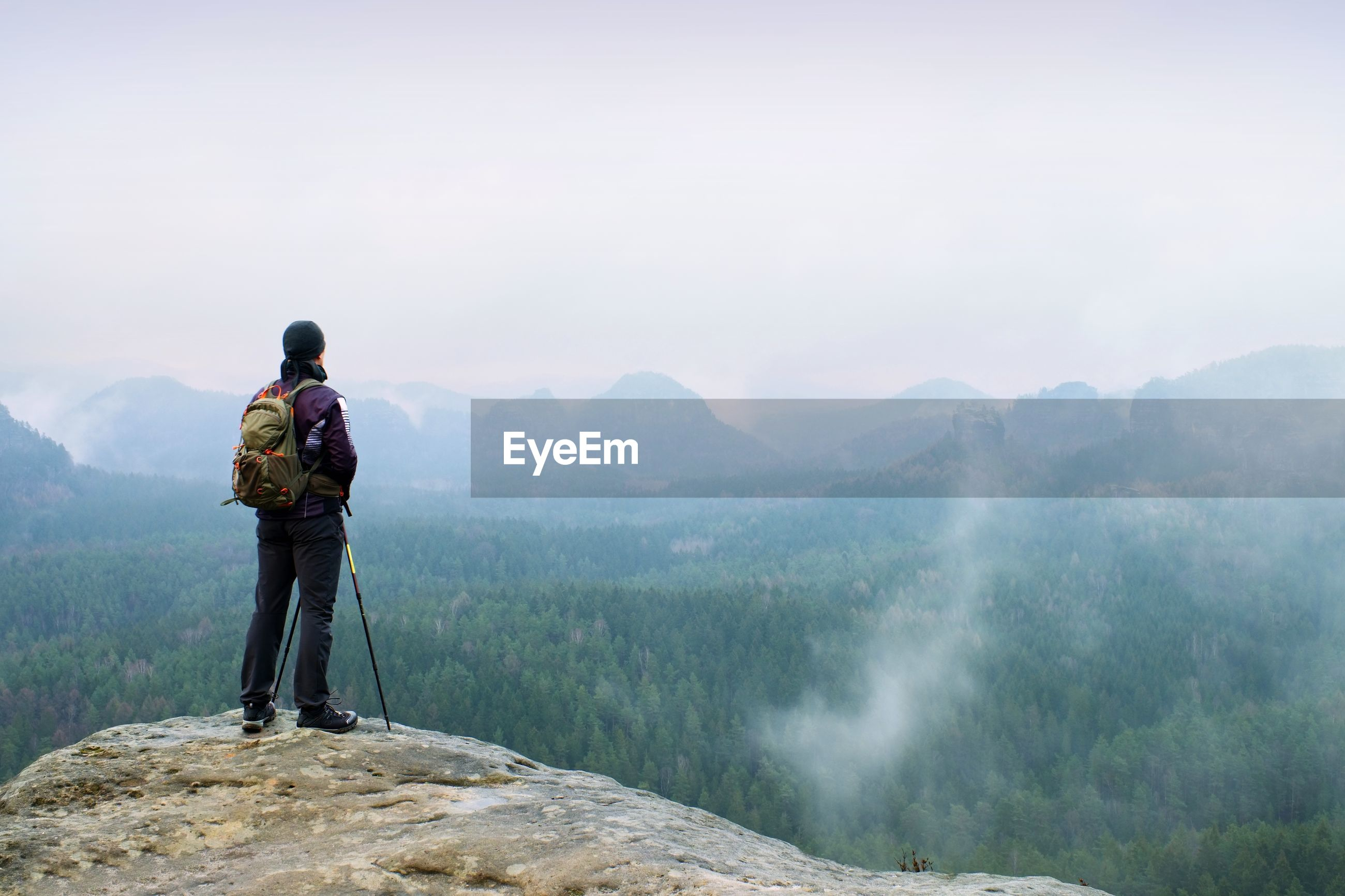 Hiker with backpack and poles on cliff rock watching over the misty and foggy spring valley.