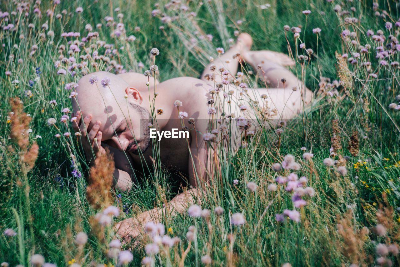 Naked Man Lying On Field