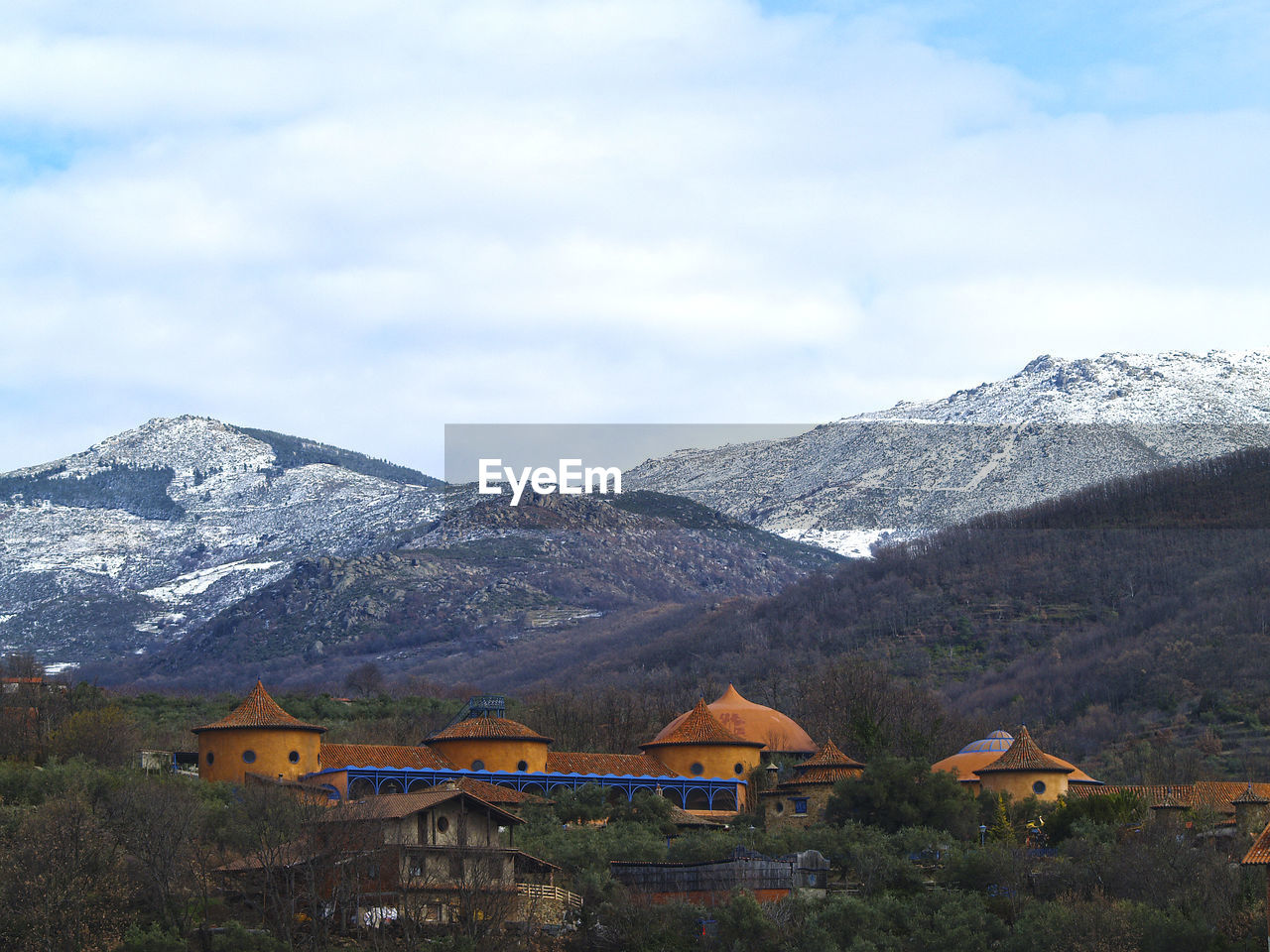 mountain, beauty in nature, mountain range, nature, sky, scenics, outdoors, day, built structure, snow, tranquility, house, building exterior, no people, architecture, landscape, cloud - sky, tree, range