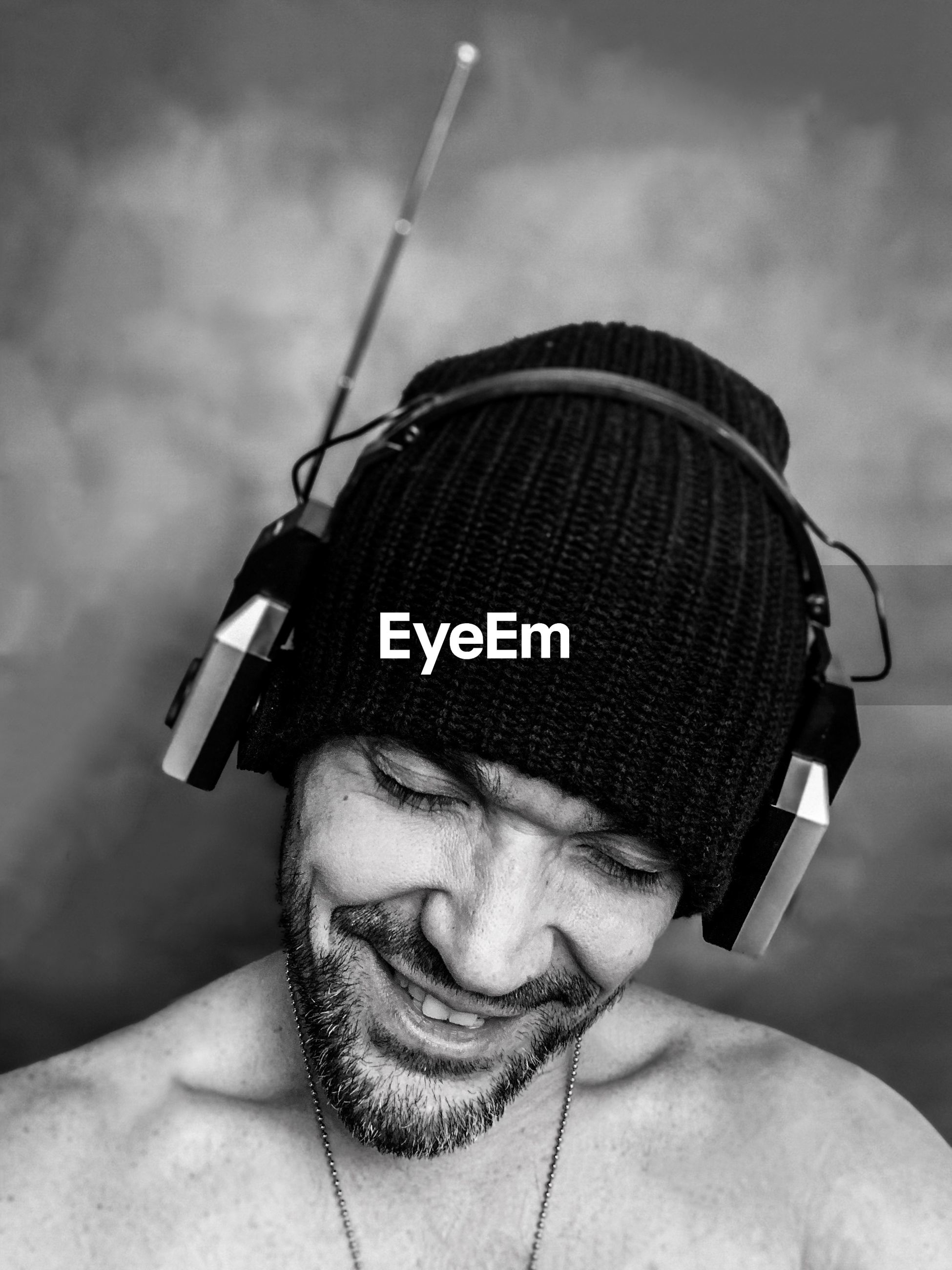 Smiling shirtless man wearing hat while listening music