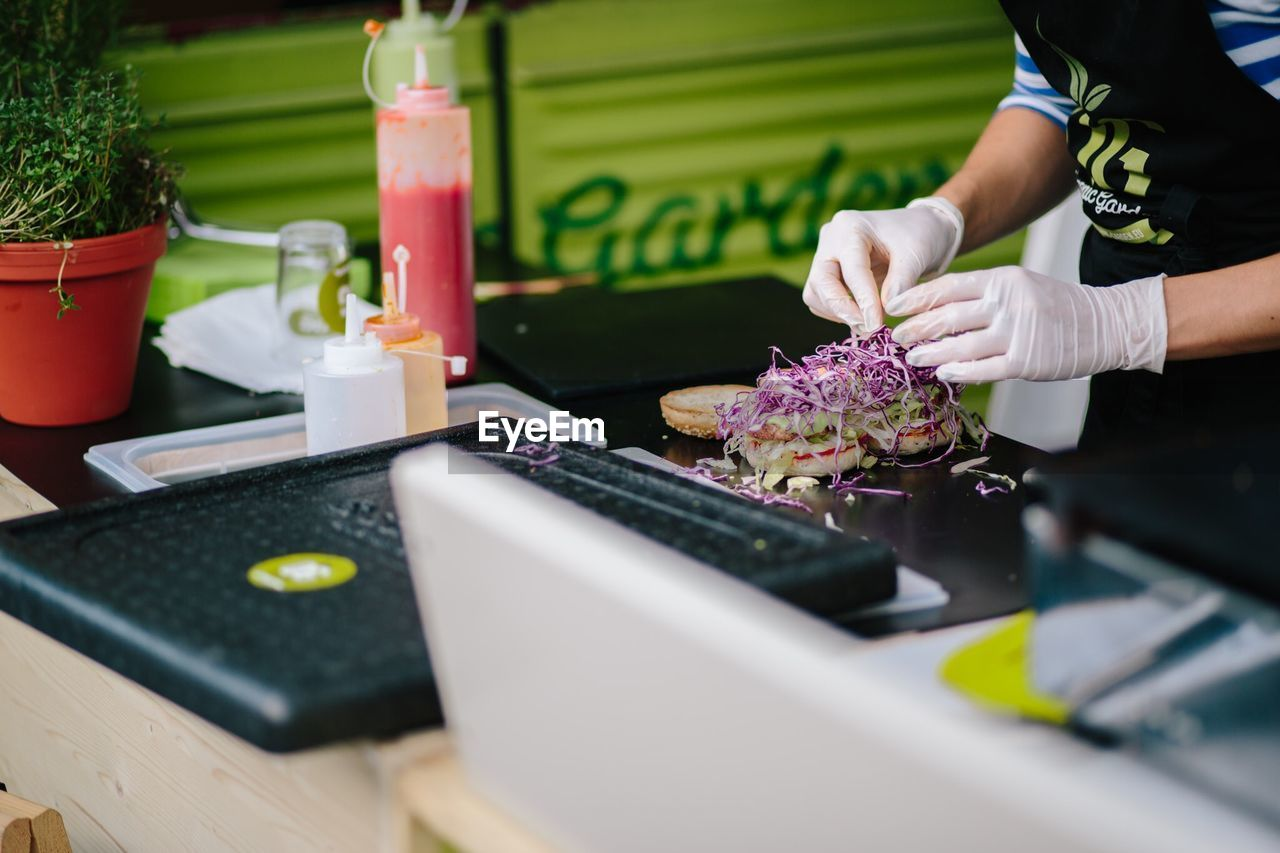 Person making burger on table