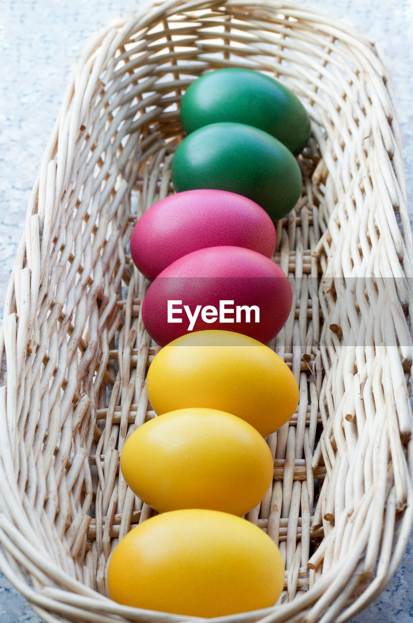 Close-up of colorful easter eggs in wicker basket on table