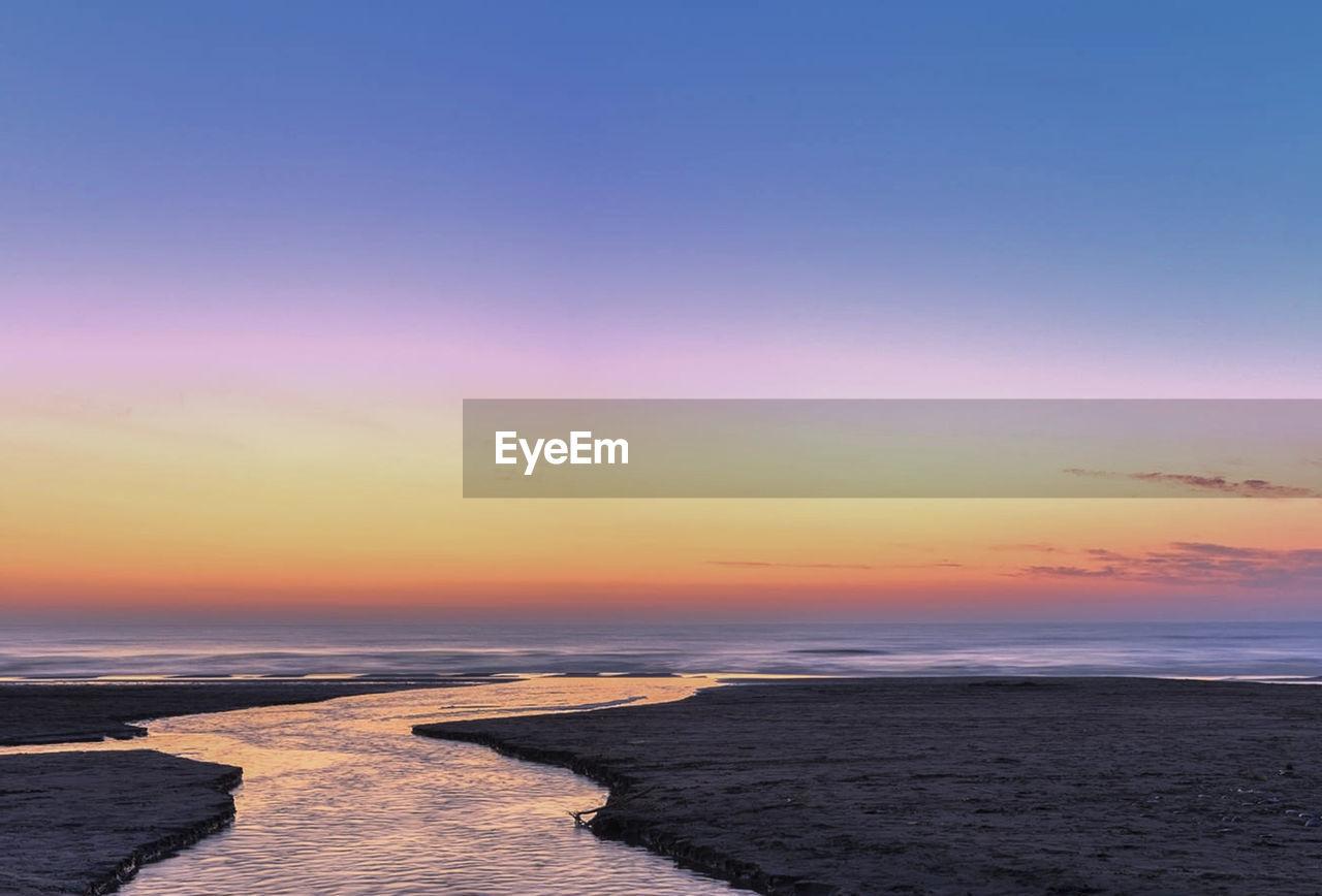 water, sea, sky, sunset, beauty in nature, scenics - nature, tranquility, tranquil scene, beach, nature, cloud - sky, land, orange color, horizon over water, horizon, no people, idyllic, outdoors, motion, purple, romantic sky