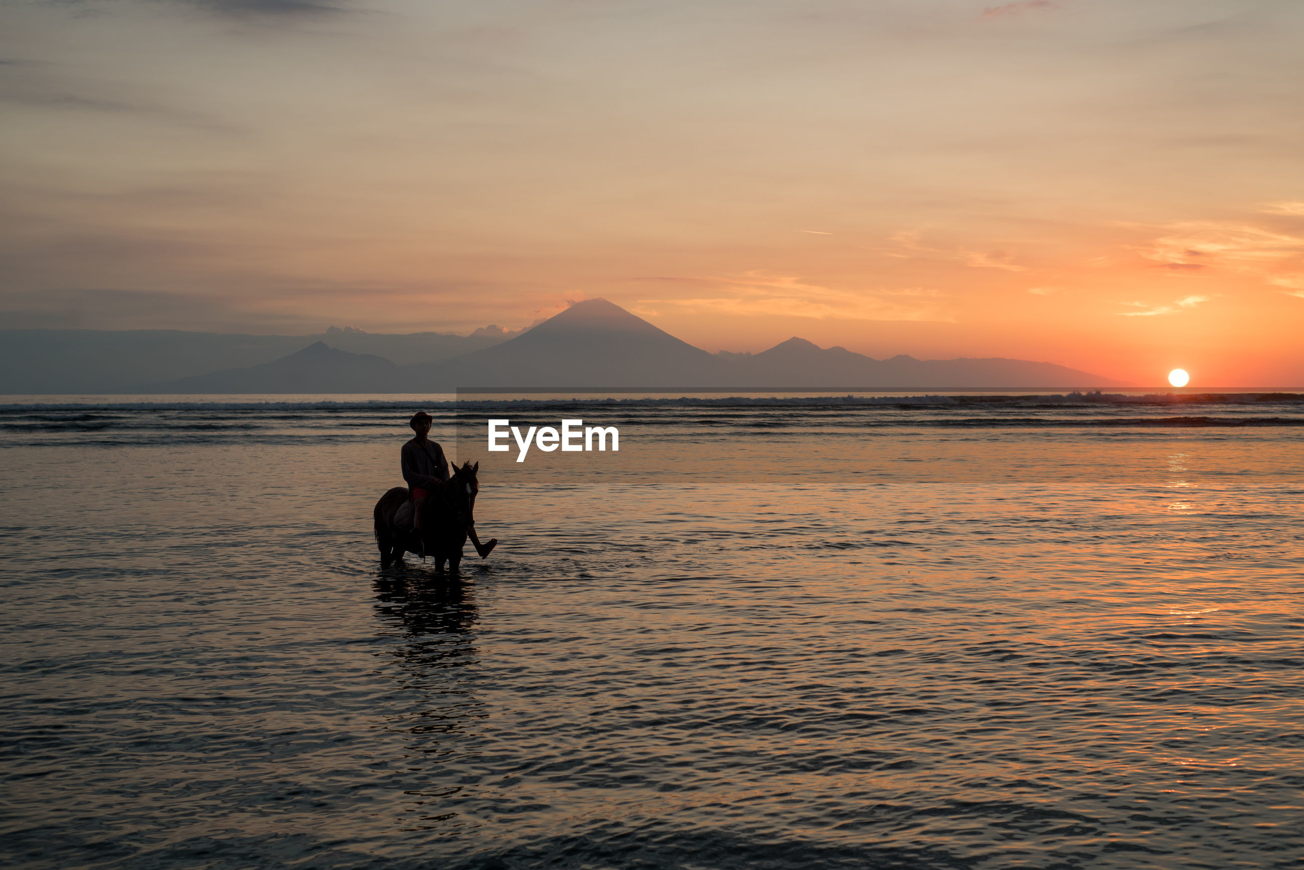Person on horse in sea against sky during sunset