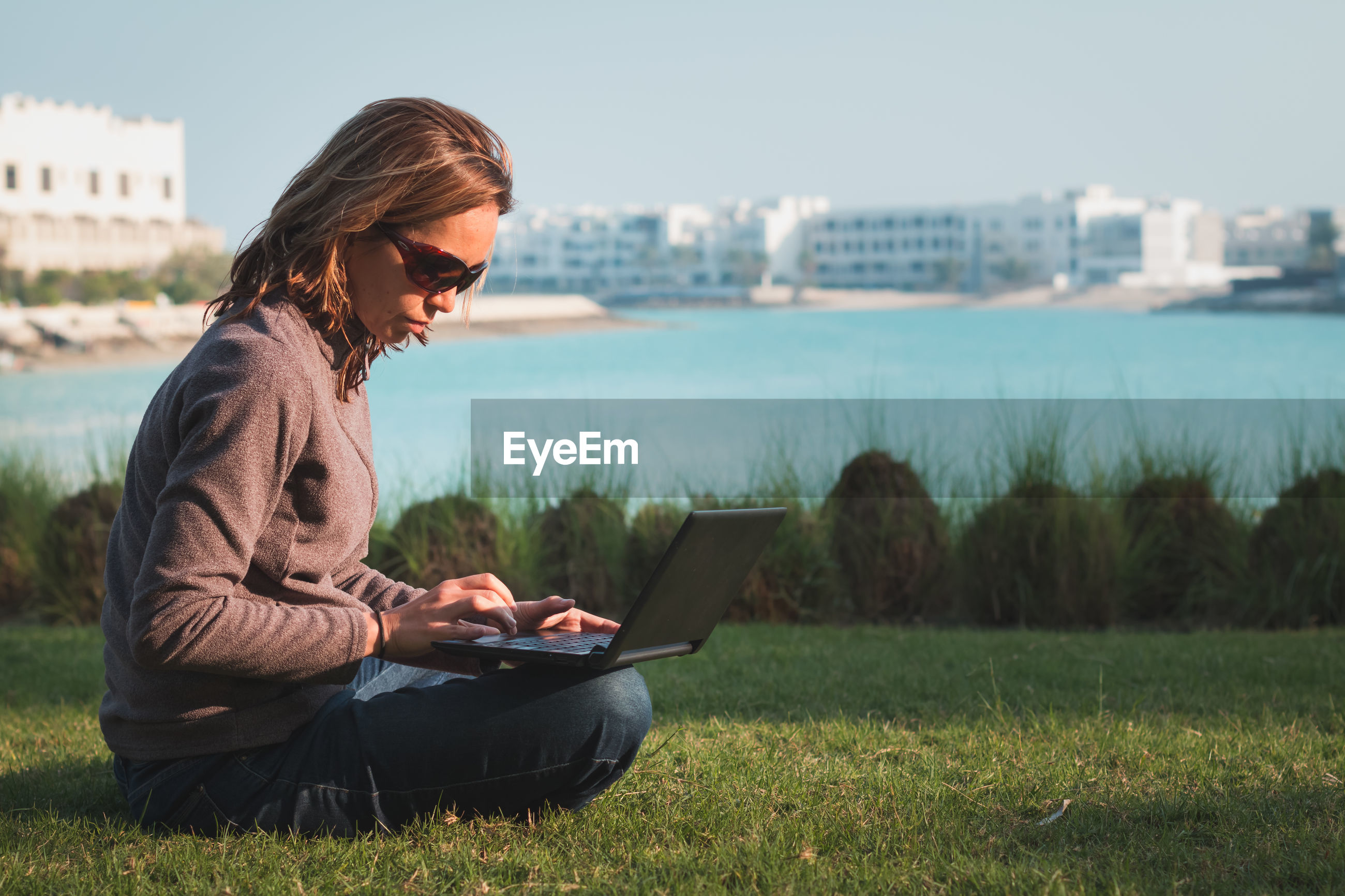 Woman working on laptop while sitting at grassy field against lake