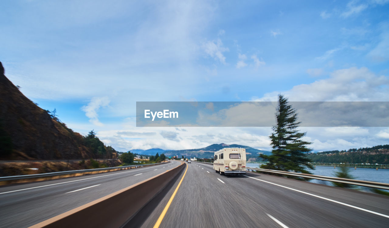 transportation, road, cloud - sky, sky, motion, mode of transportation, nature, mountain, road marking, sign, car, direction, marking, motor vehicle, day, symbol, the way forward, no people, land vehicle, highway, outdoors, road trip, dividing line