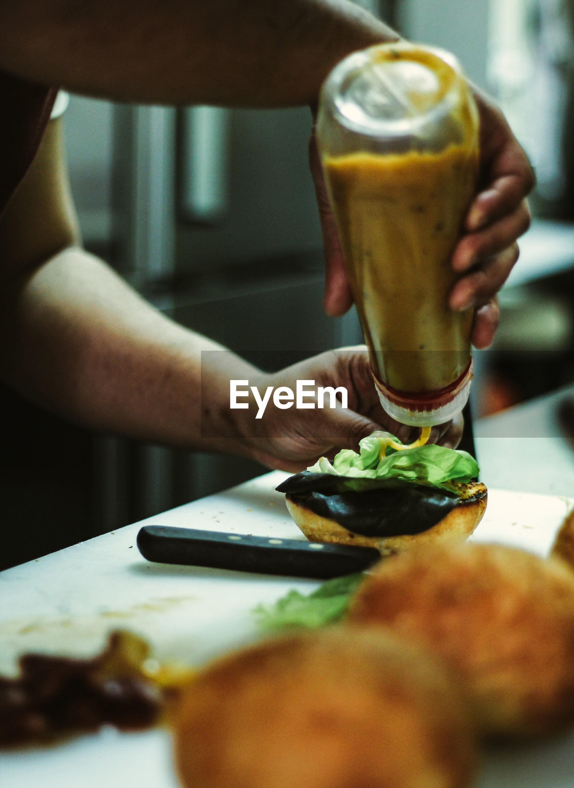 Close-up of hand preparing a burger