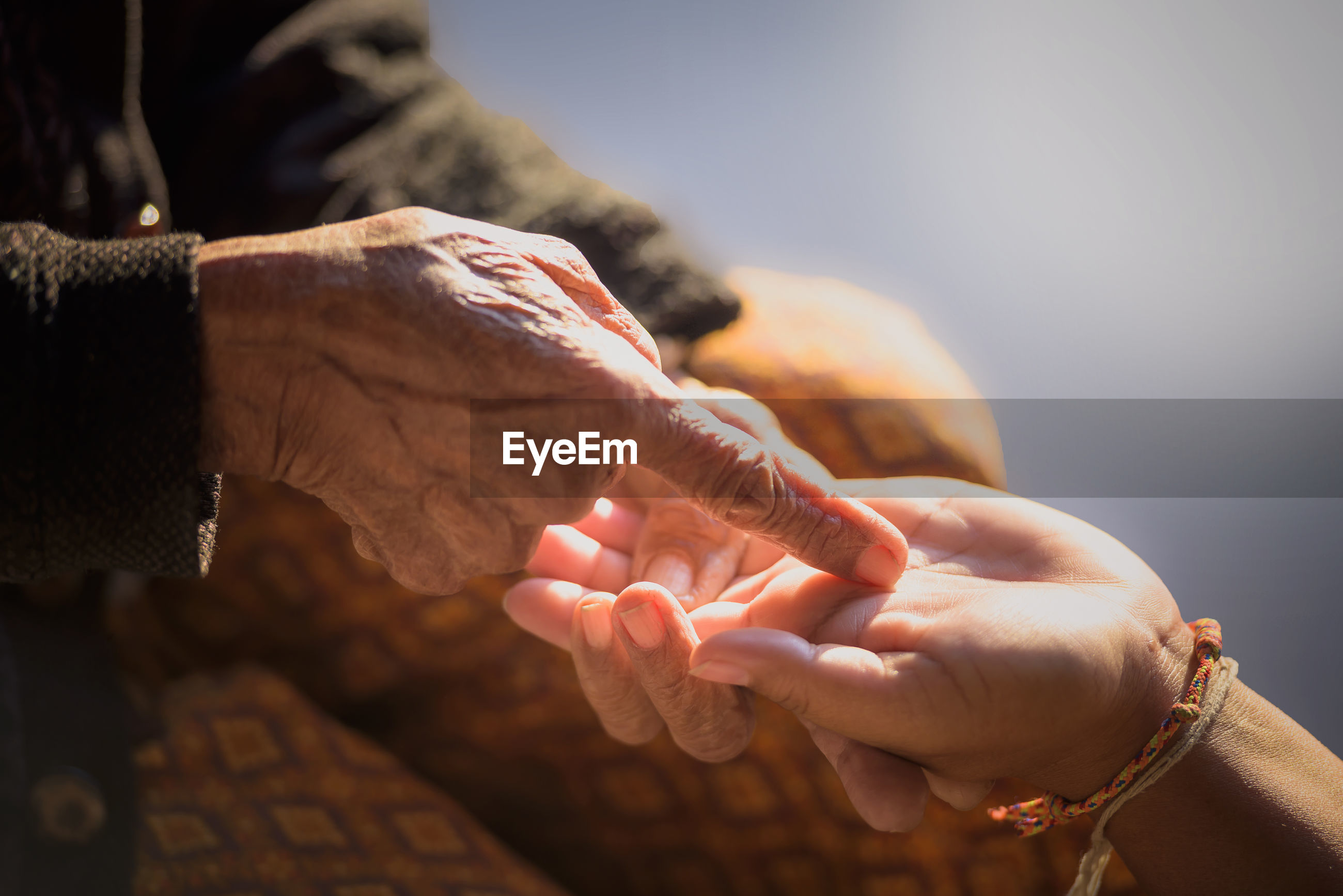 The hands of old women and young women, taking care of the elderly closely.