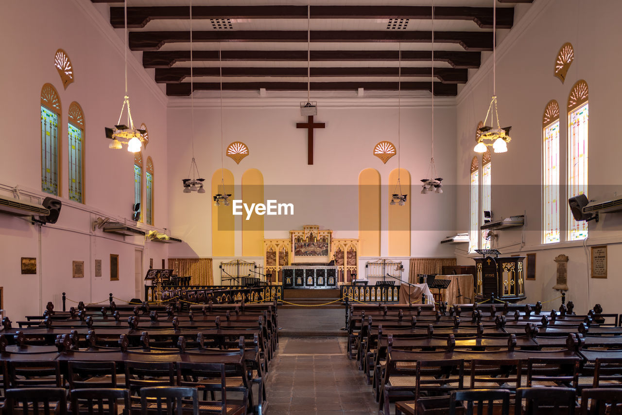 religion, seat, place of worship, belief, spirituality, architecture, indoors, chair, built structure, absence, in a row, pew, building, table, no people, empty, lighting equipment, ceiling, aisle