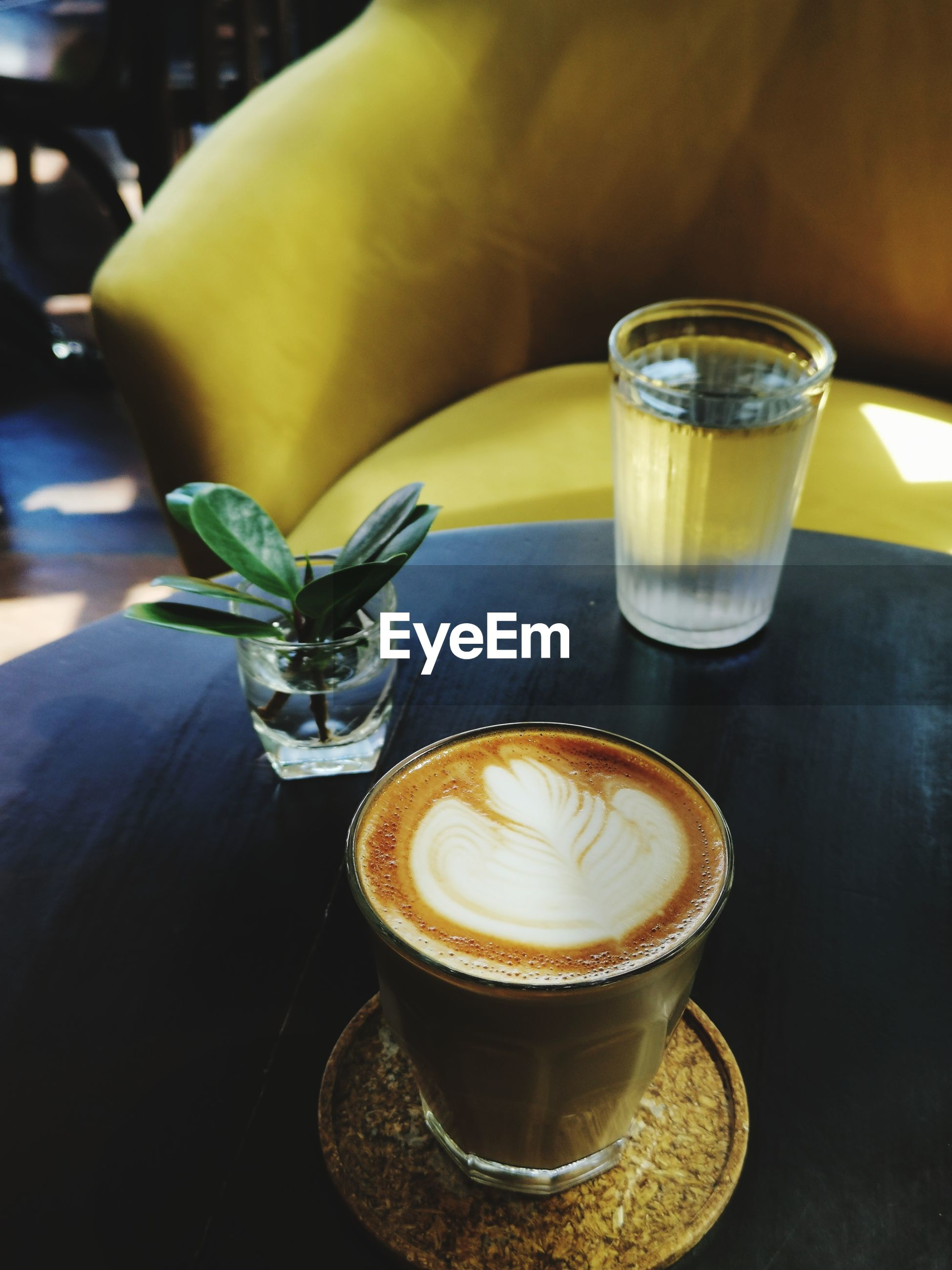 CLOSE-UP OF COFFEE CUP WITH DRINK ON TABLE