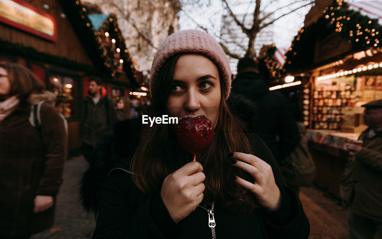 Portrait of woman holding candy apple in christmas market