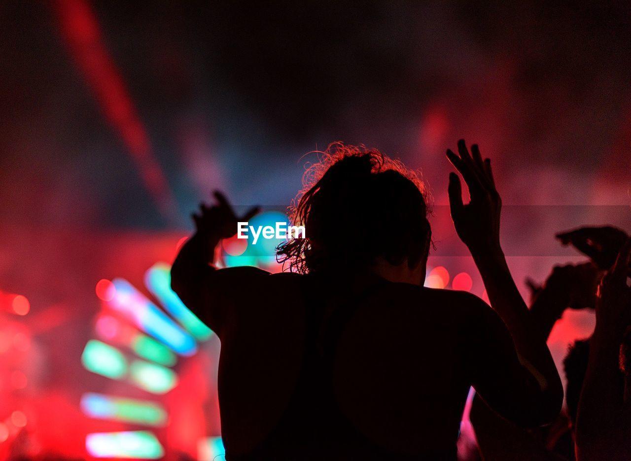 Rear View Of Man Enjoying At Music Concert