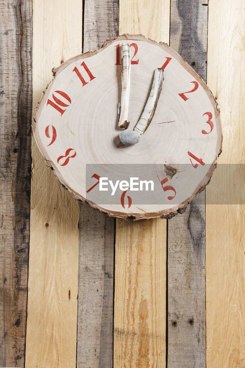 Close-up of clock hanging on wooden wall