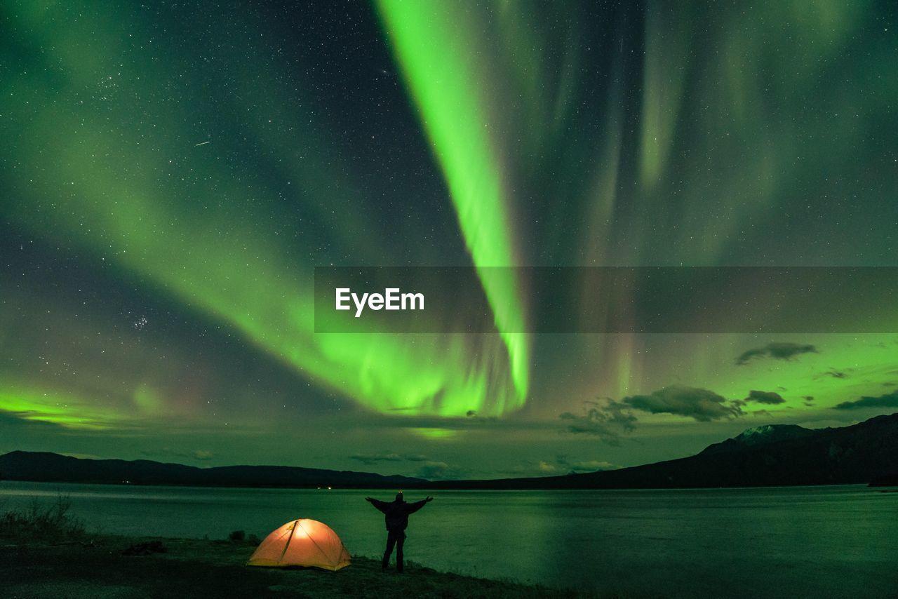 Rear View Of Man At Lakeshore Against Aurora Polaris