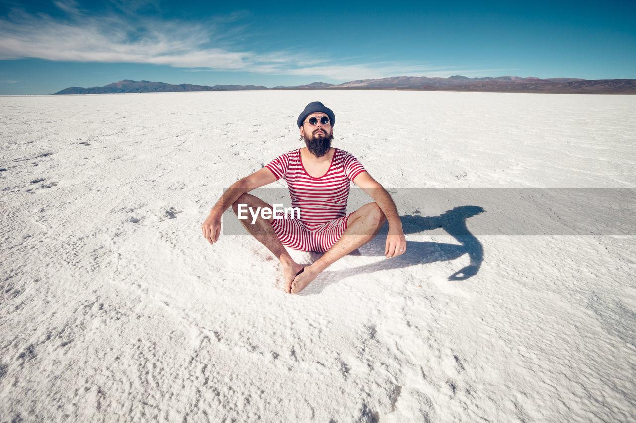 Full Length Of Man Sitting On Sand At Beach
