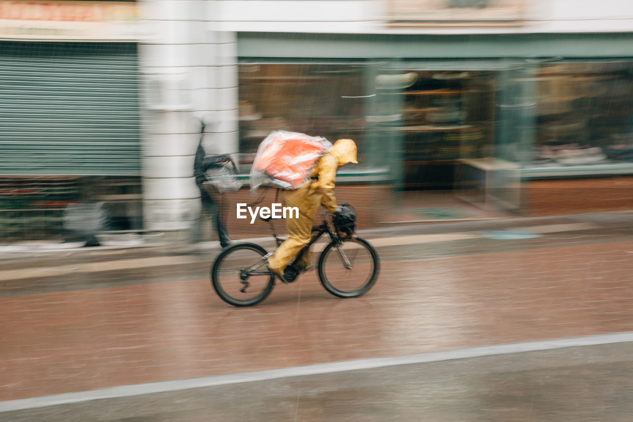 motion, transportation, blurred motion, bicycle, mode of transportation, architecture, building exterior, land vehicle, city, activity, built structure, sport, ride, riding, speed, people, on the move, full length, day, men, outdoors