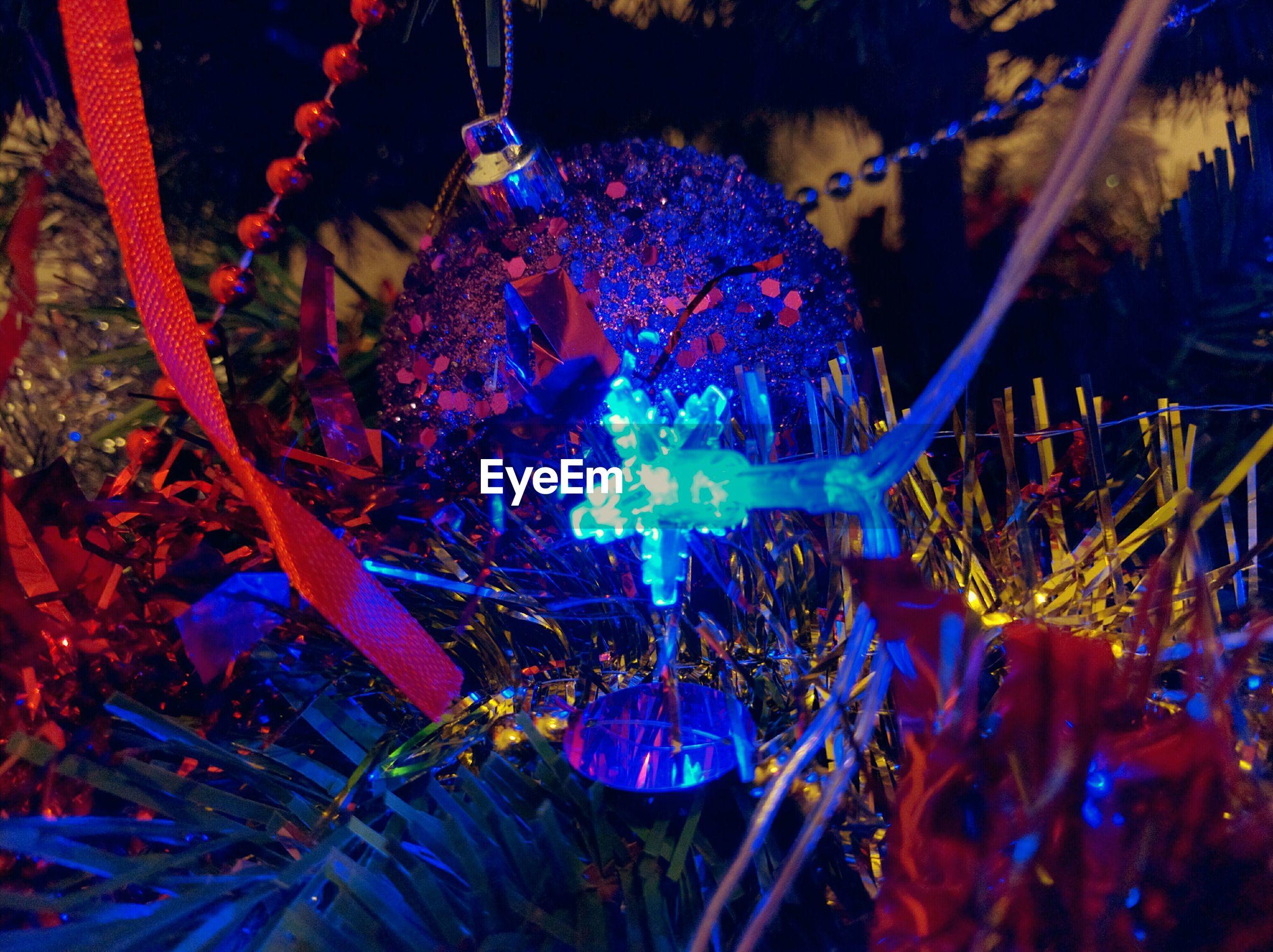 Close-up of decorations on illuminated christmas tree