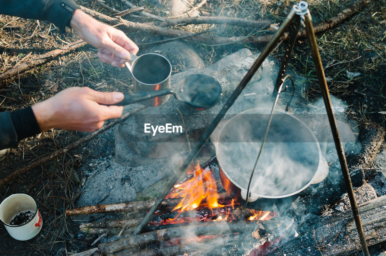Cropped hands of man preparing food on fire at campsite