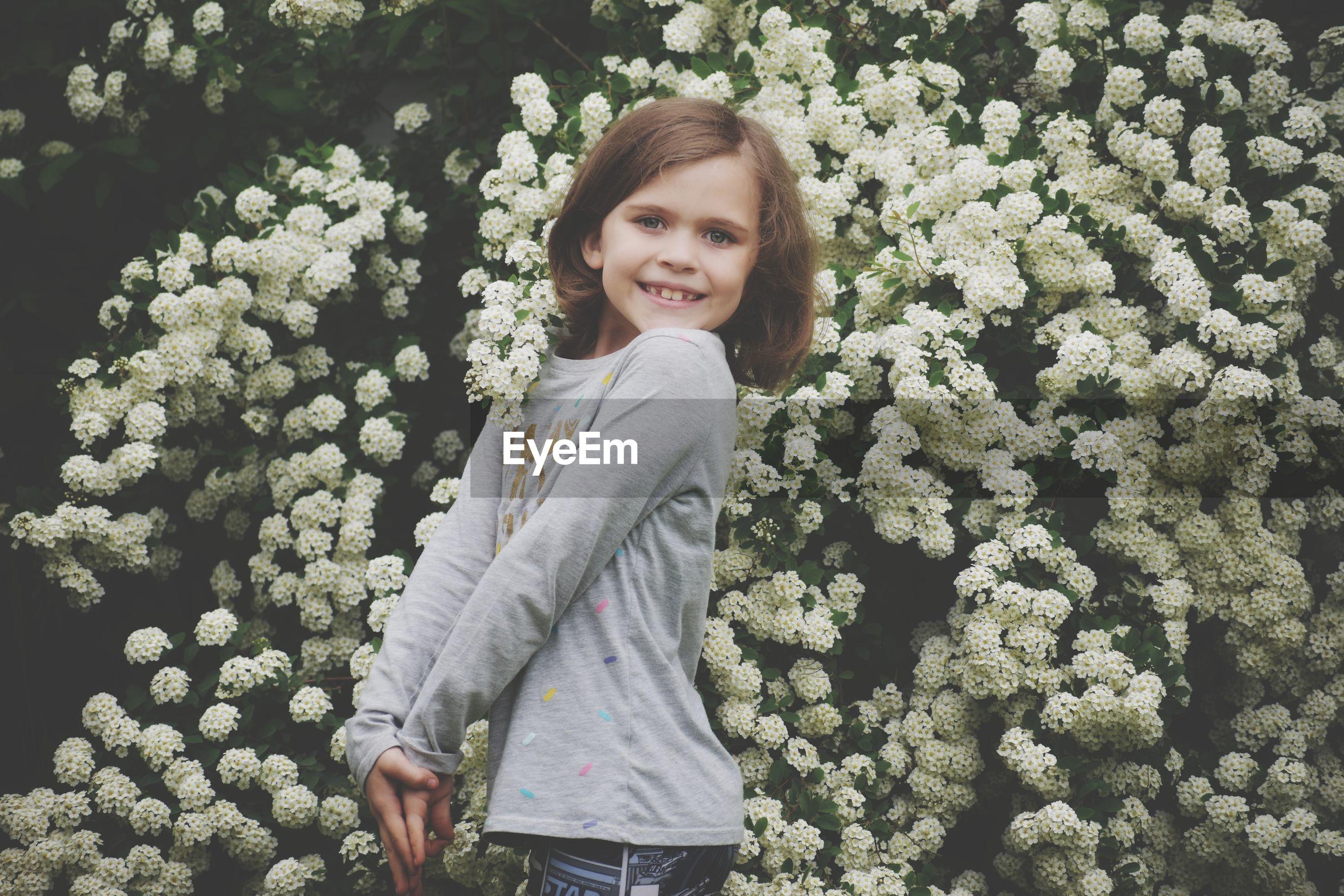 Portrait of smiling girl standing against flowering plants