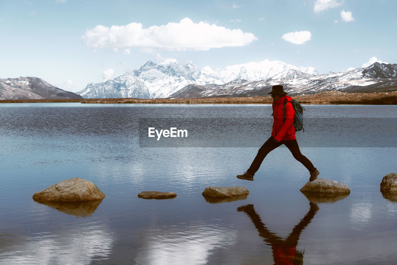 mountain, one person, scenics - nature, beauty in nature, full length, real people, water, snow, reflection, sky, lake, leisure activity, winter, lifestyles, mountain range, day, cold temperature, tranquil scene, snowcapped mountain, outdoors