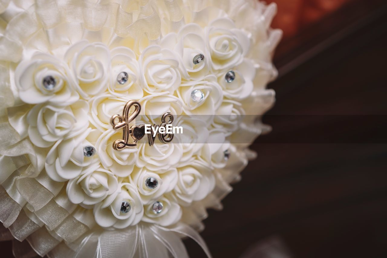 flower, flowering plant, close-up, plant, beauty in nature, vulnerability, celebration, petal, fragility, no people, inflorescence, event, life events, wedding, freshness, flower head, white color, selective focus, focus on foreground, indoors, personal accessory