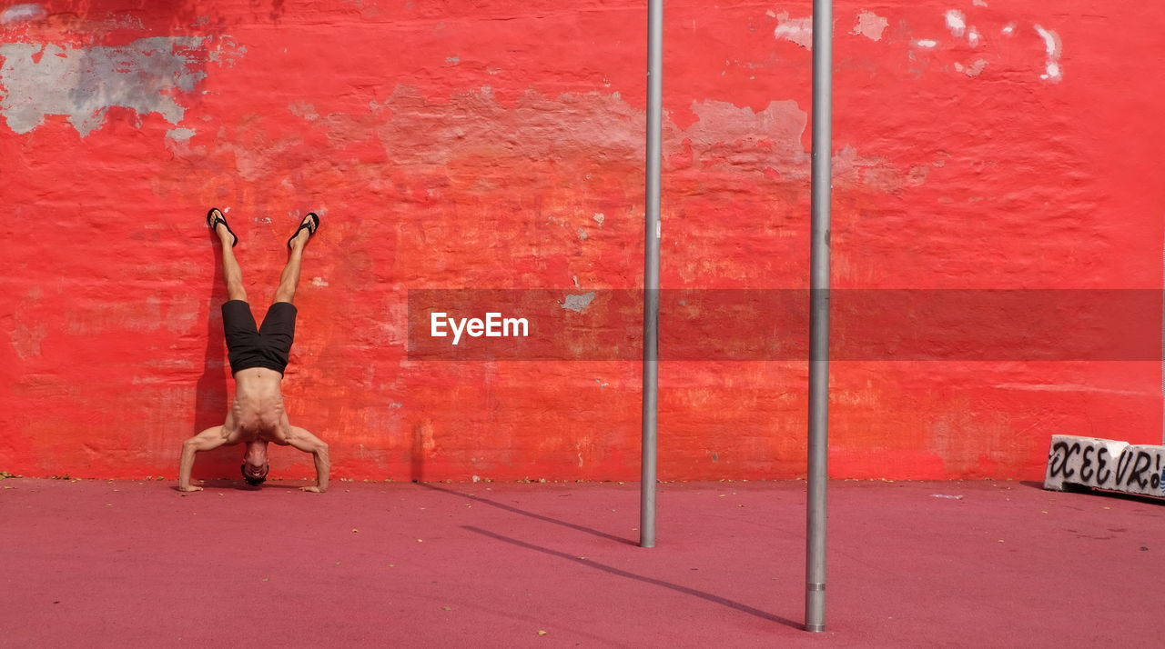 Full Length Of Shirtless Man Doing Handstand Against Red Wall