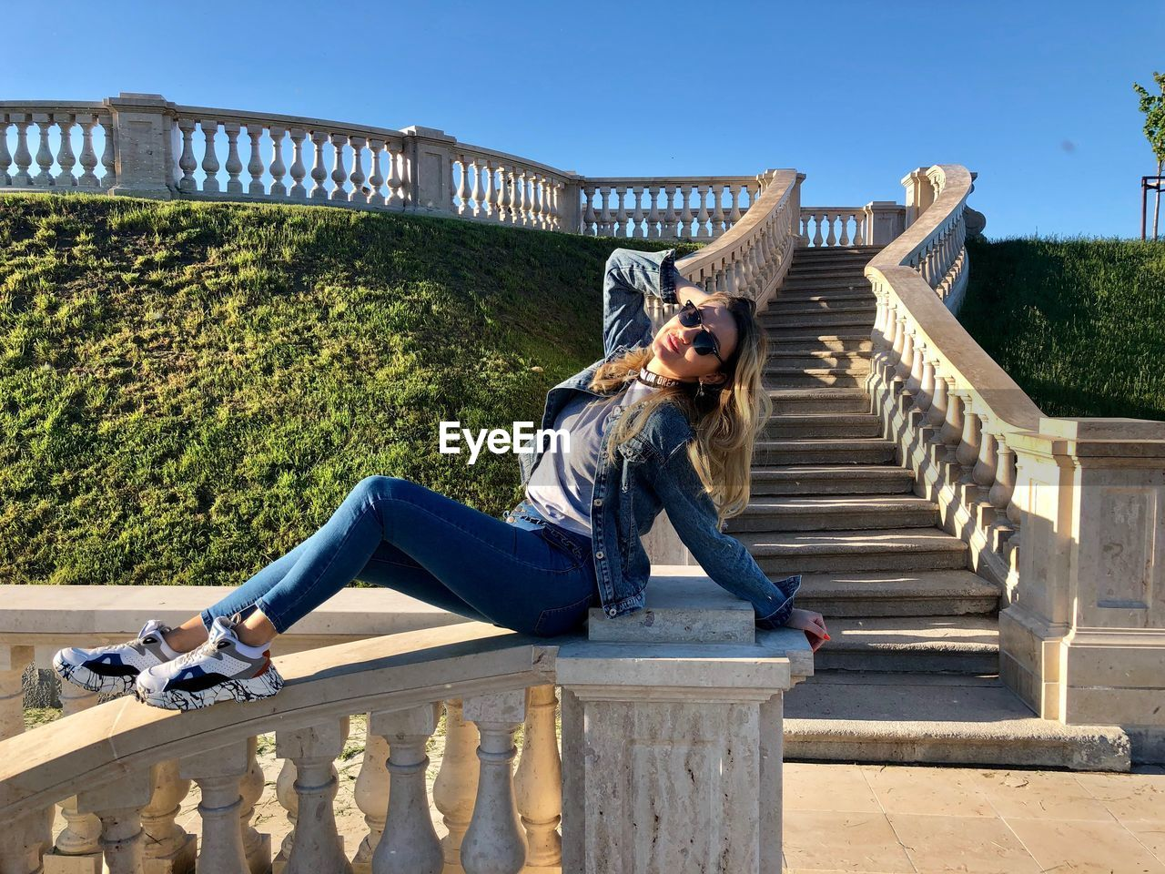 one person, full length, architecture, real people, leisure activity, lifestyles, young adult, casual clothing, built structure, railing, sunglasses, day, fashion, sunlight, nature, glasses, staircase, young women, bridge, outdoors, footbridge, hairstyle