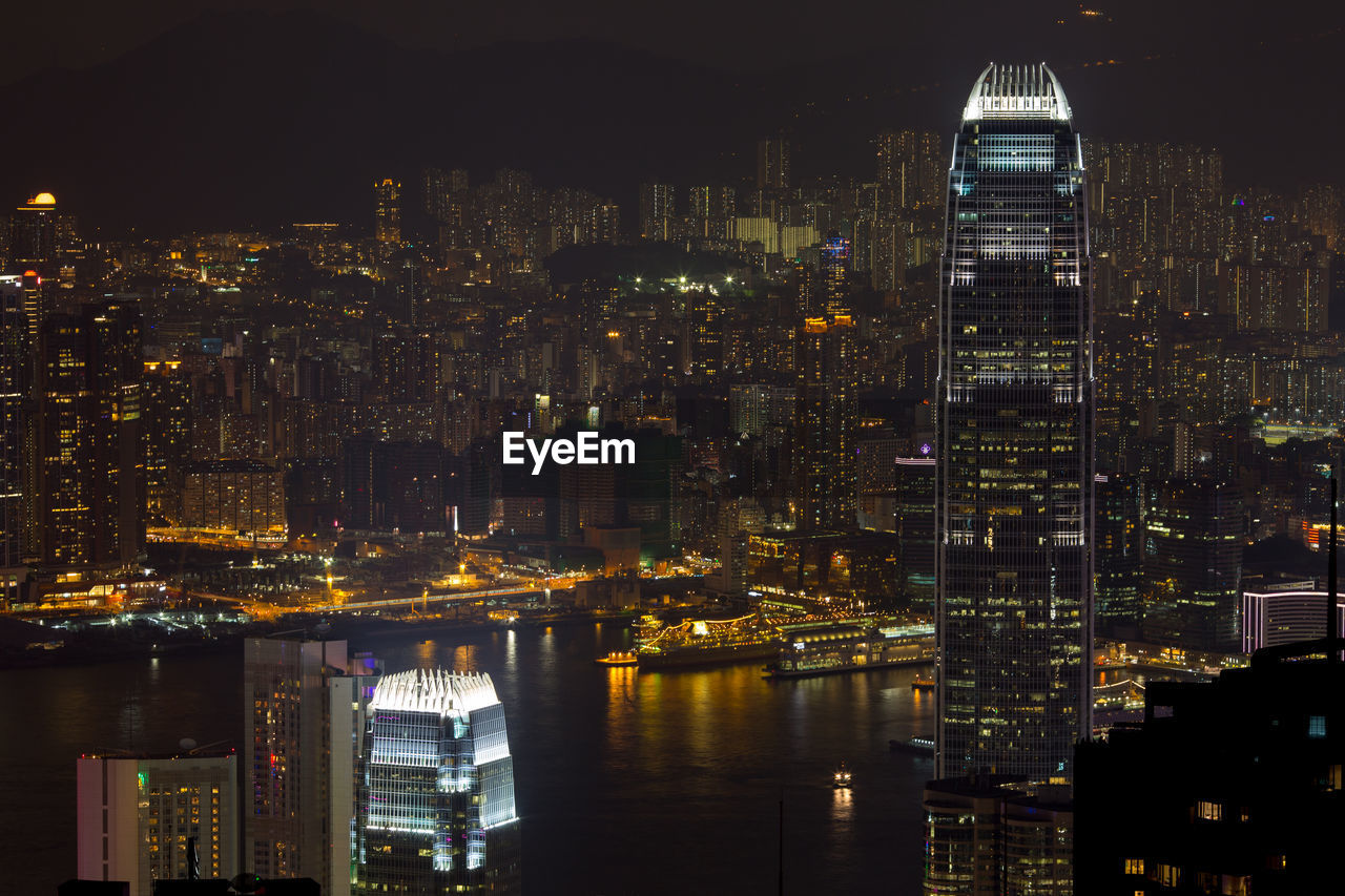Buildings At Victoria Harbour In Illuminated City At Night
