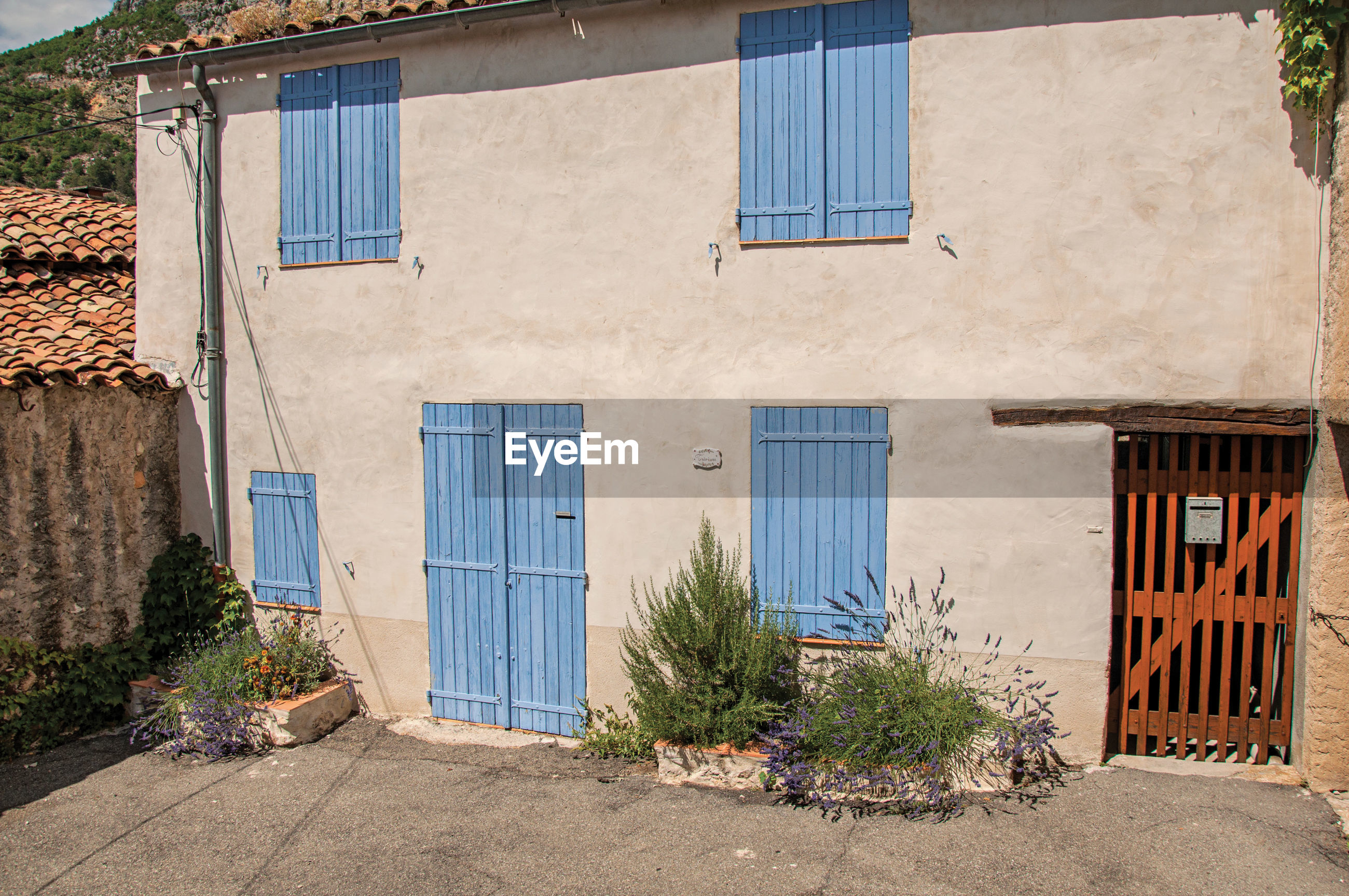 View of house with blue shutters closed at moustiers-sainte-marie, in the french provence.