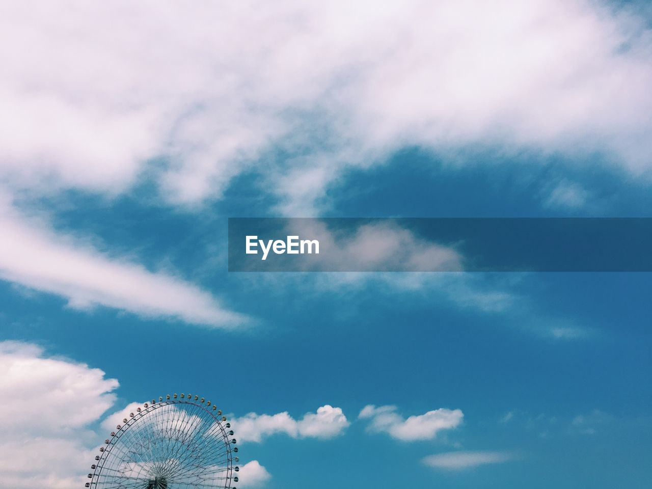 Low Angle View Of Ferris Wheel Against Cloudy Blue Sky