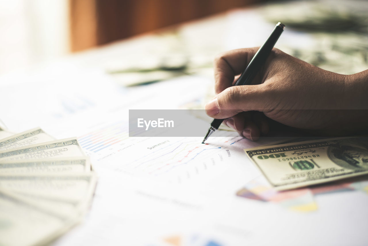 Close-up of businessman working over graph with money on table