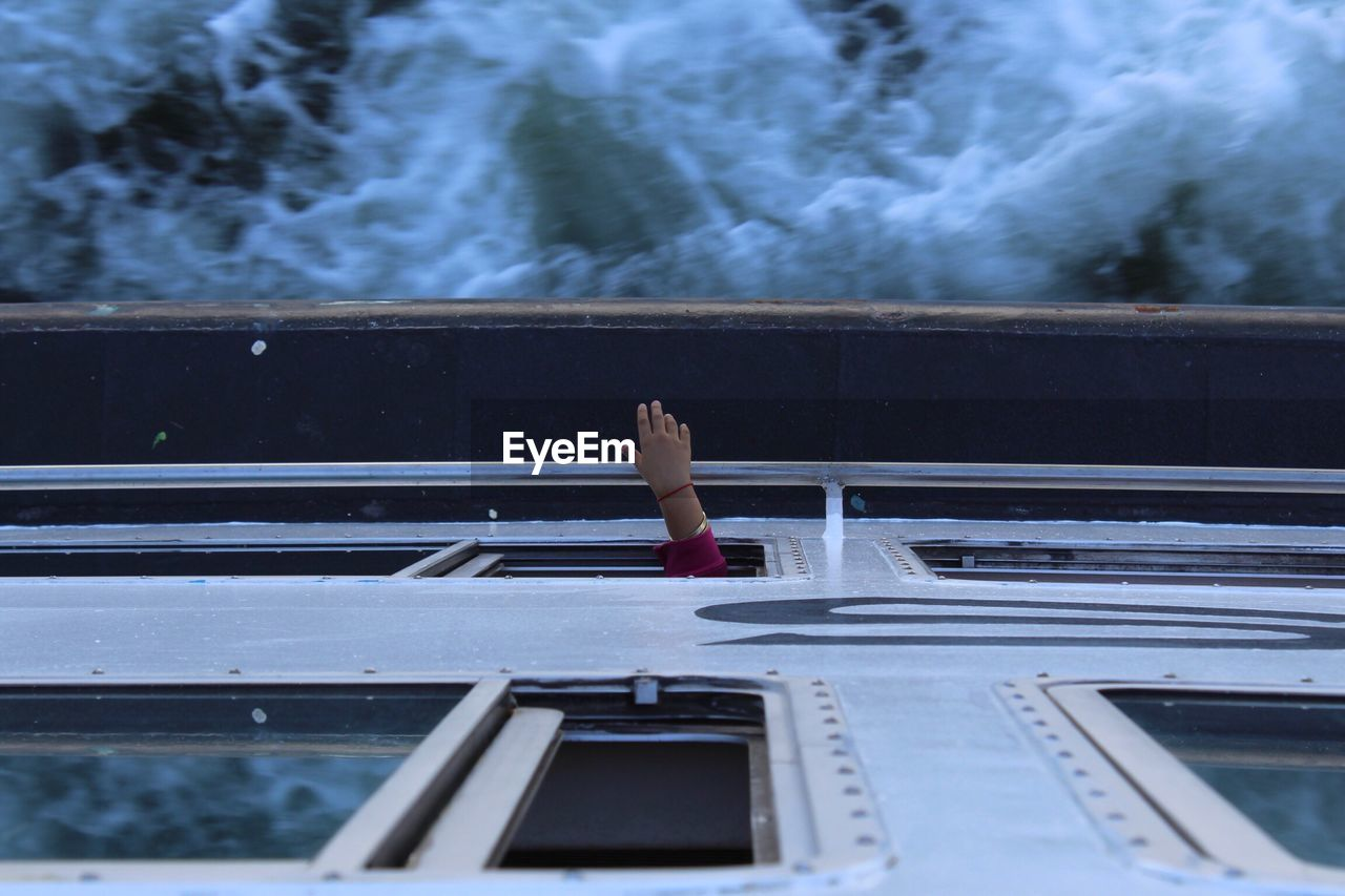 Cropped Hand Of Person At Window In Ferry On Sea