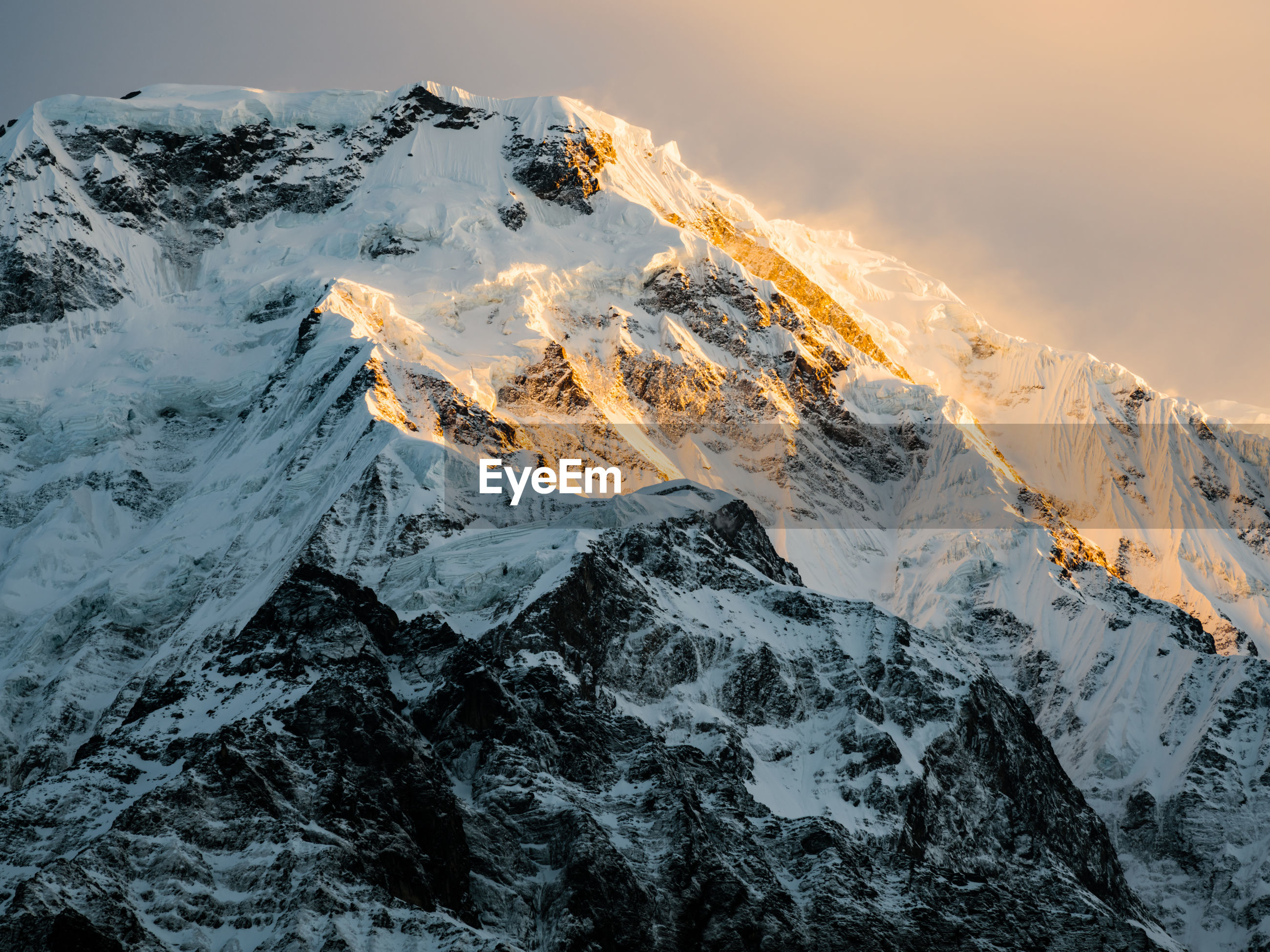 The summit of annapurna south at sunrise, sunlight shining on the snowcapped ridges on the peak.