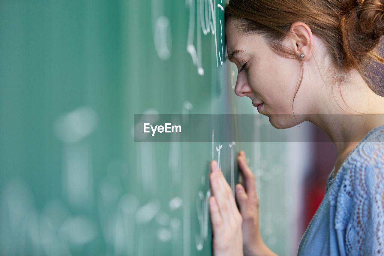 Woman with headache by blackboard in classroom