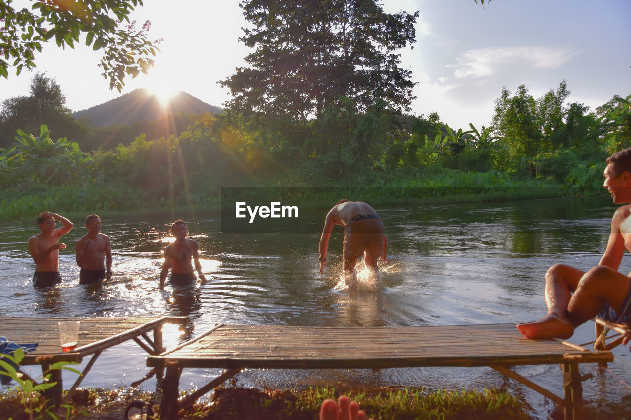 water, group of people, tree, sky, real people, nature, plant, lifestyles, leisure activity, men, lake, sunlight, enjoyment, day, women, togetherness, beauty in nature, people, lens flare, sun, outdoors