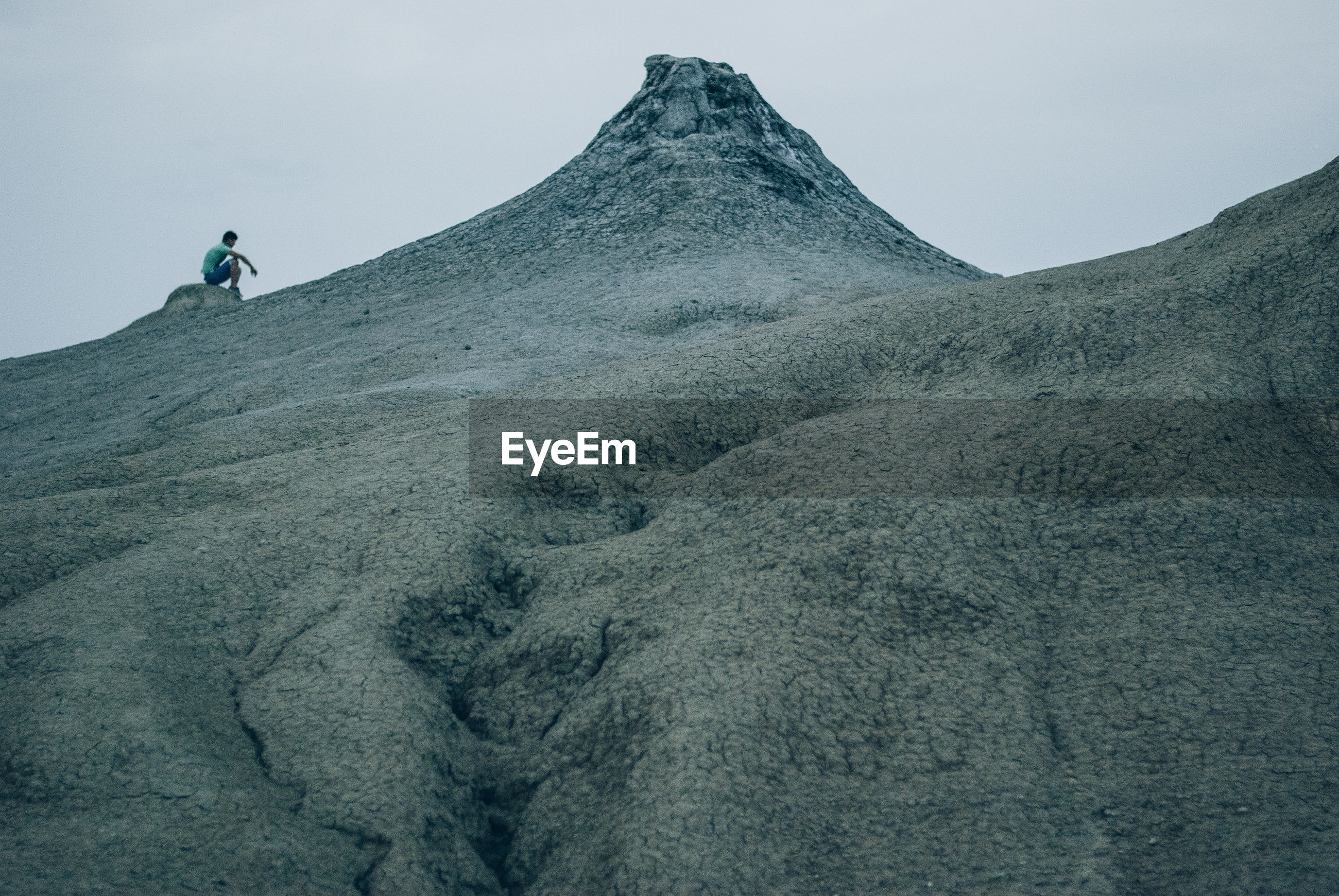 Low angle view of man sitting on mountain against sky