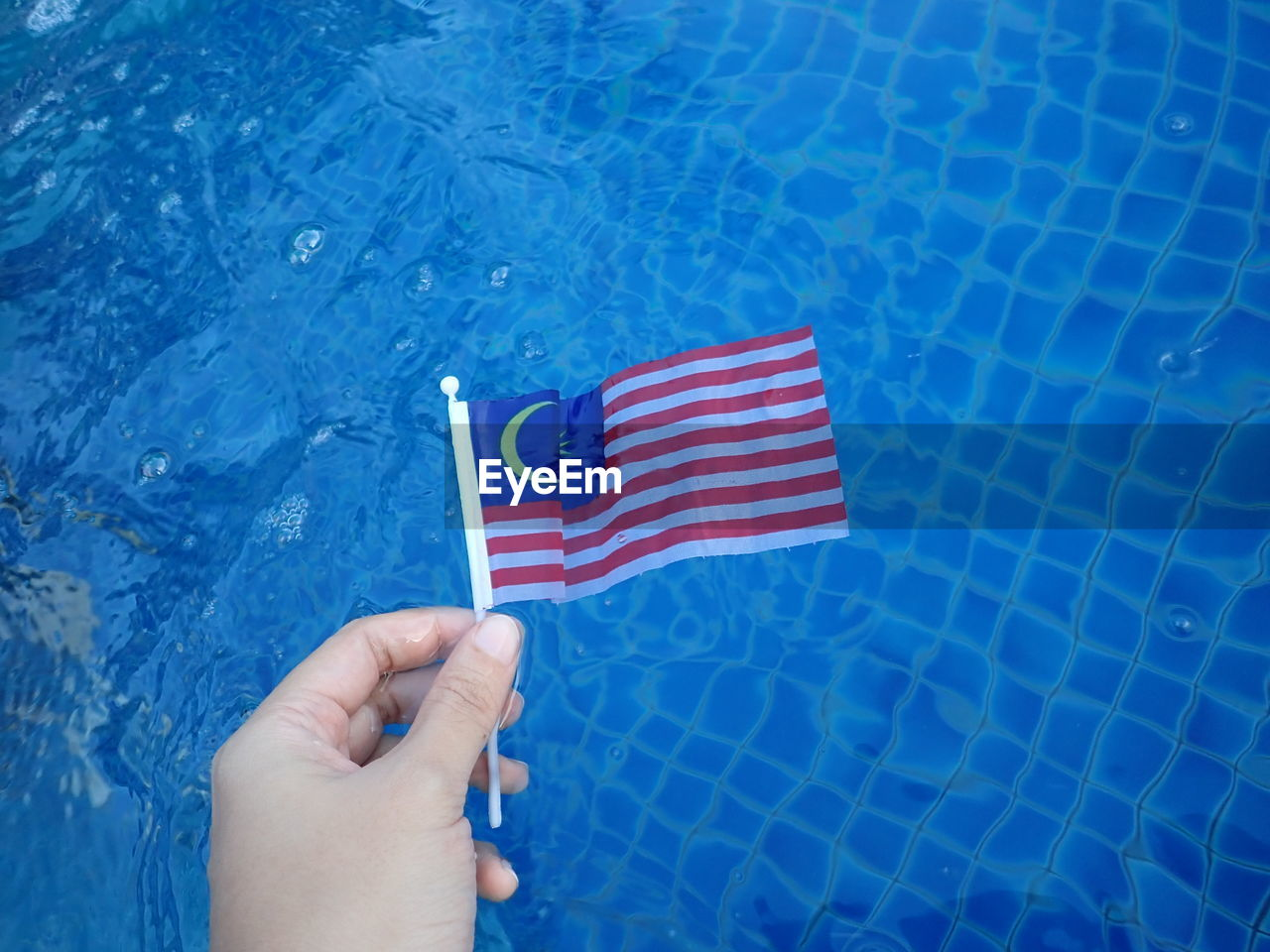 flag, human hand, human body part, striped, hand, patriotism, blue, one person, real people, unrecognizable person, body part, red, holding, water, day, finger, outdoors, swimming pool, national icon, human limb