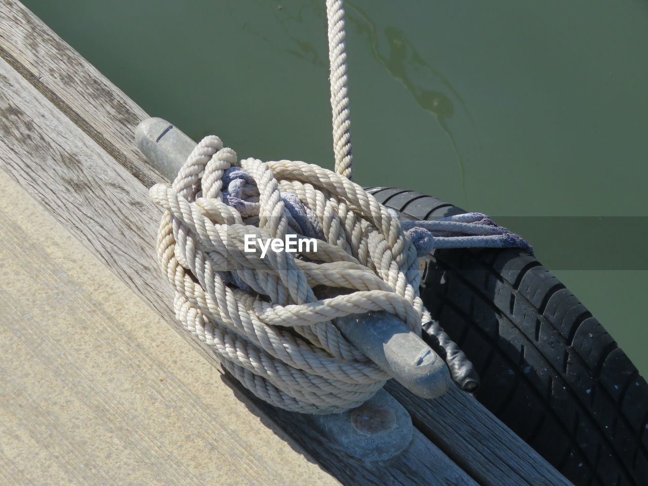 High Angle View Of Rope Tied On Bollard At Pier By River During Sunny Day