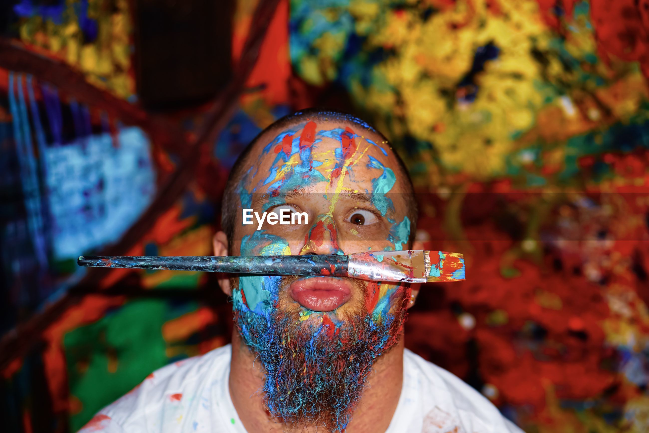 Portrait of funny man with messy painted face and paintbrush