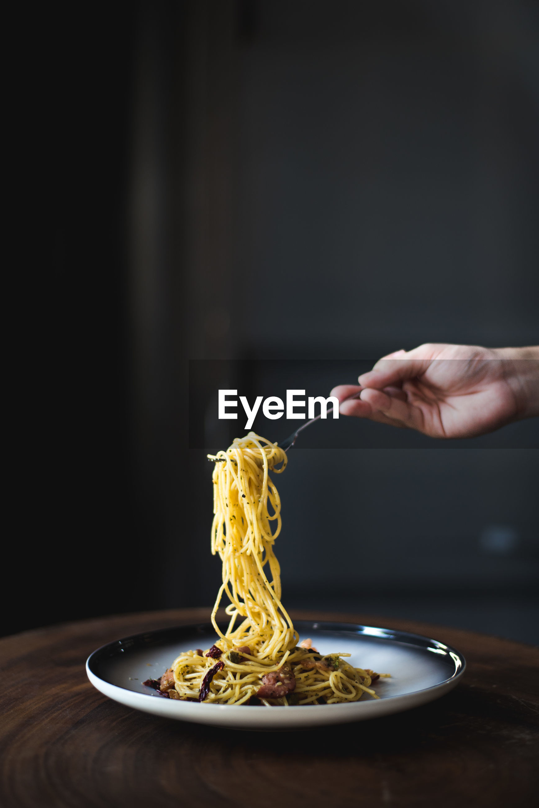 Noodles in fork held by person