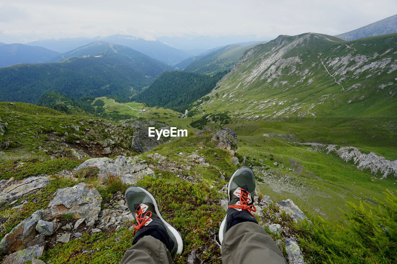 Low Section Of Hiker Relaxing On Grassy Mountain