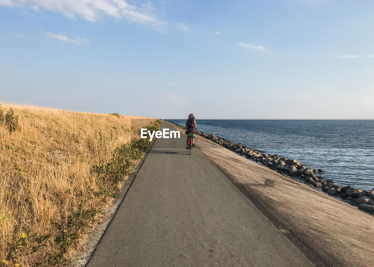 Rear view of woman riding bicycle on road by sea
