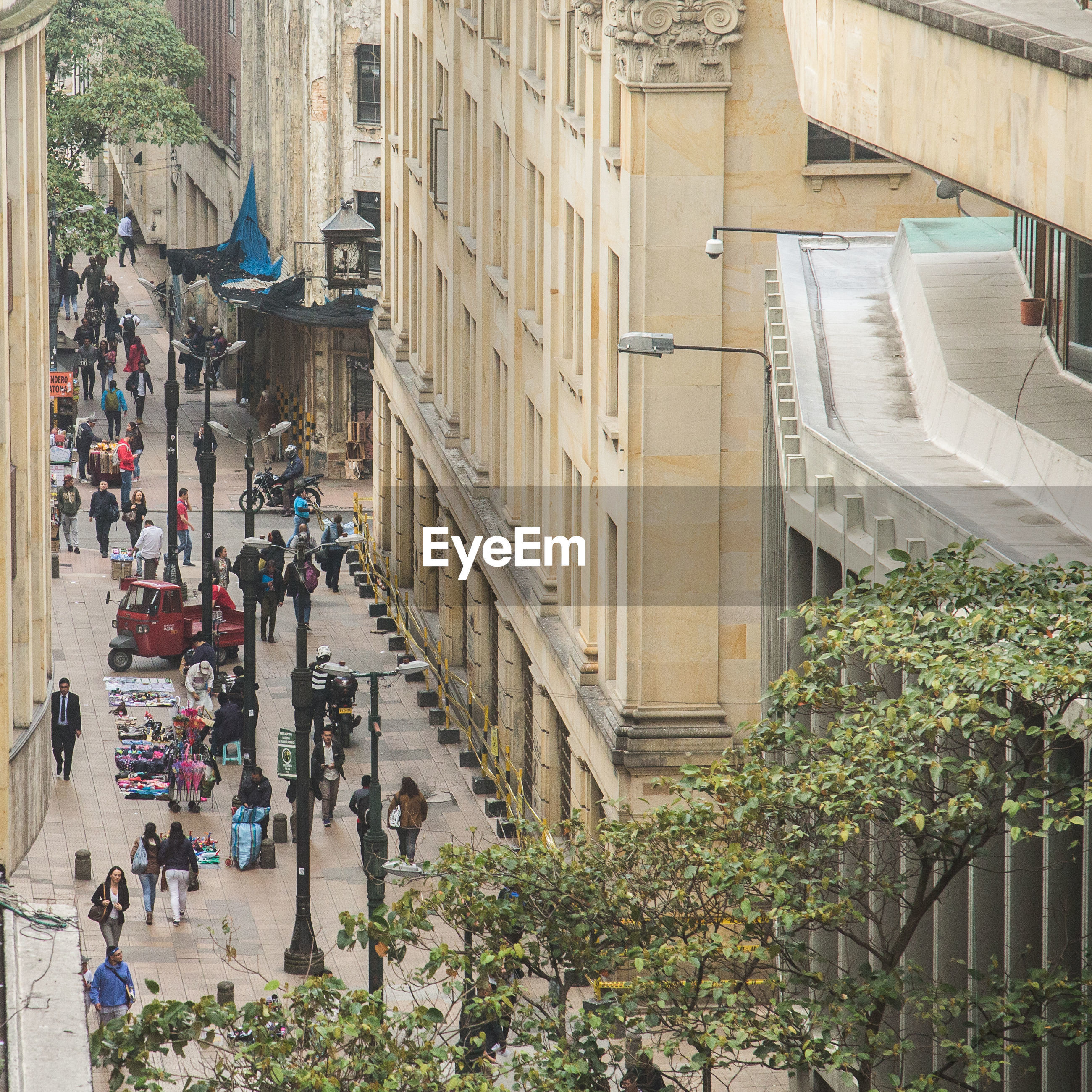 HIGH ANGLE VIEW OF PEOPLE ON STREET BY BUILDINGS