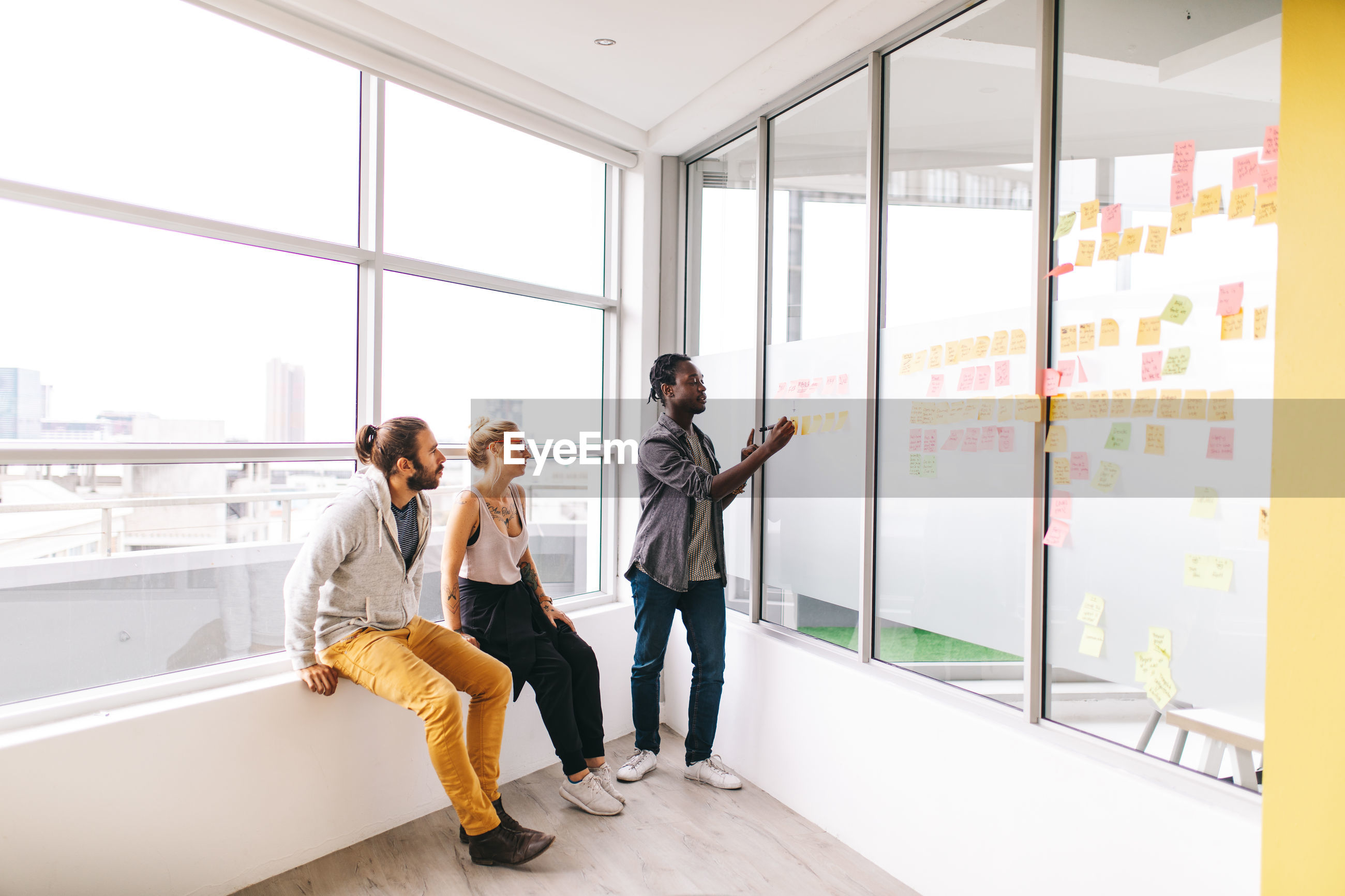 Colleagues looking at businessman writing on adhesive notes over window in office