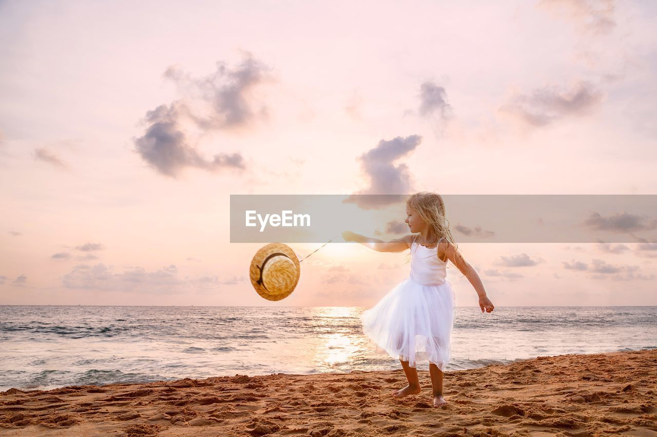 sky, beach, sea, land, real people, one person, full length, water, lifestyles, leisure activity, sunset, women, beauty in nature, cloud - sky, horizon over water, scenics - nature, motion, horizon, hairstyle, outdoors