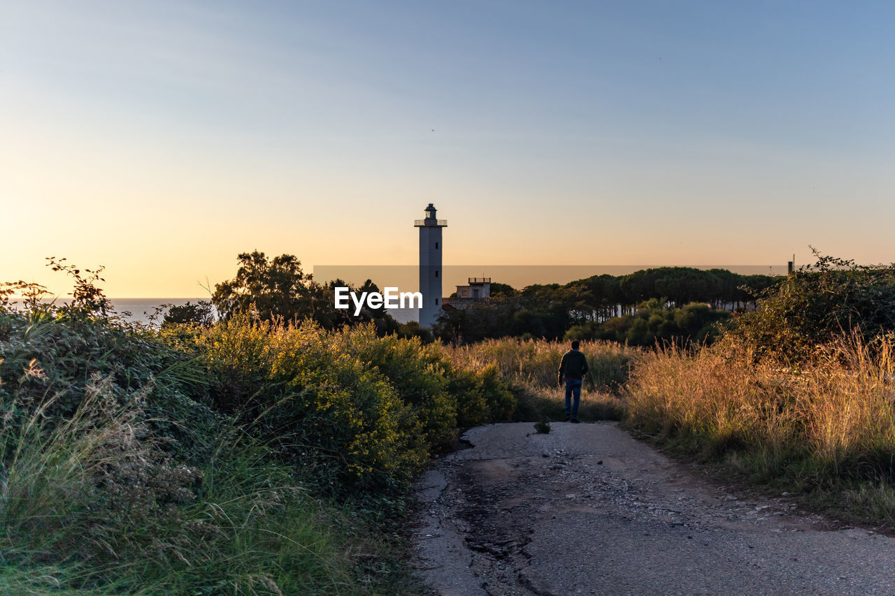 sky, direction, built structure, building exterior, plant, architecture, tower, nature, guidance, lighthouse, land, building, sunset, beauty in nature, scenics - nature, real people, water, grass, growth, tranquility, outdoors