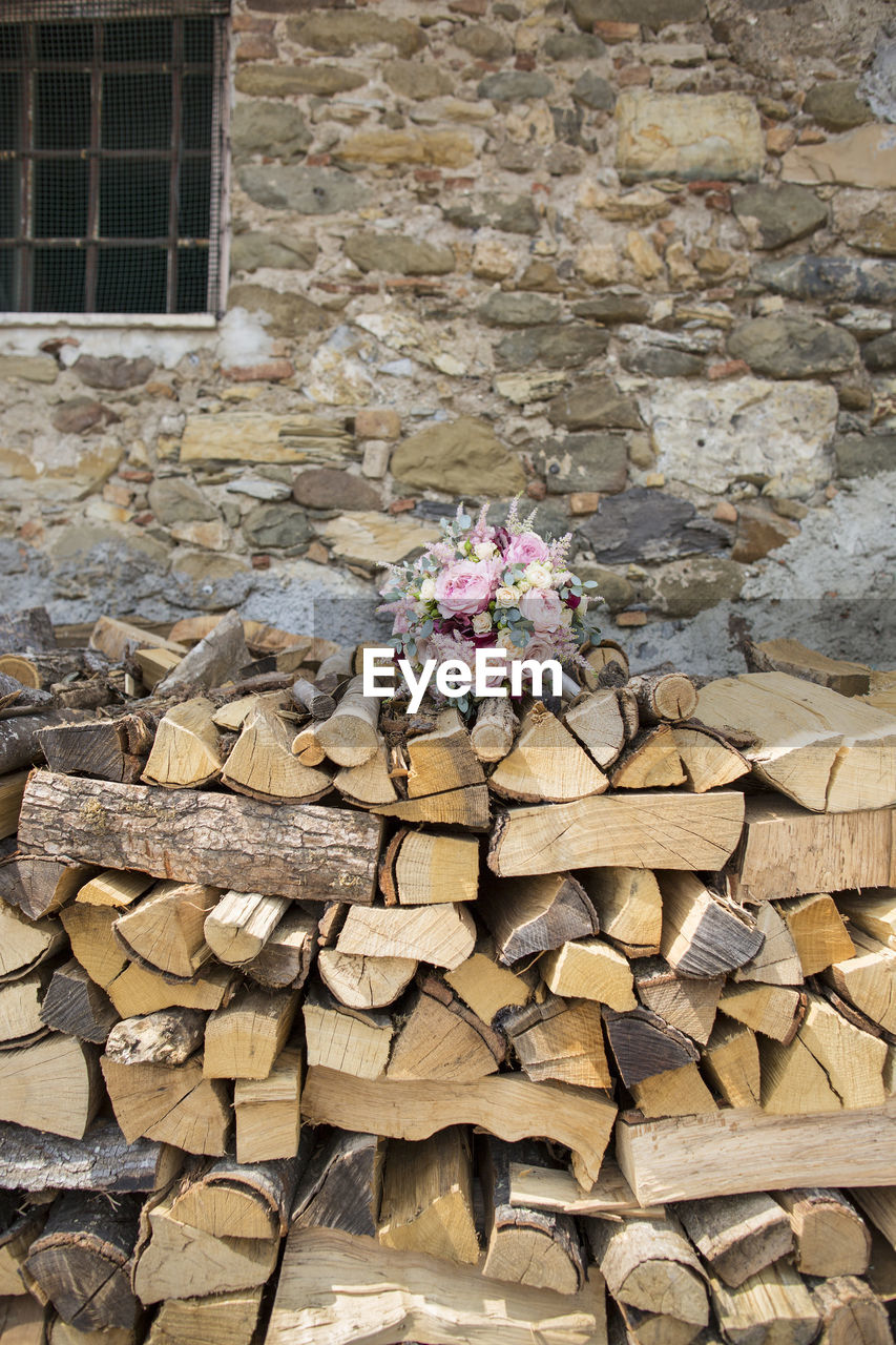 stack, log, large group of objects, abundance, timber, day, firewood, wood - material, wood, heap, built structure, architecture, building exterior, no people, nature, woodpile, outdoors, brick, wall, environmental issues, stone wall