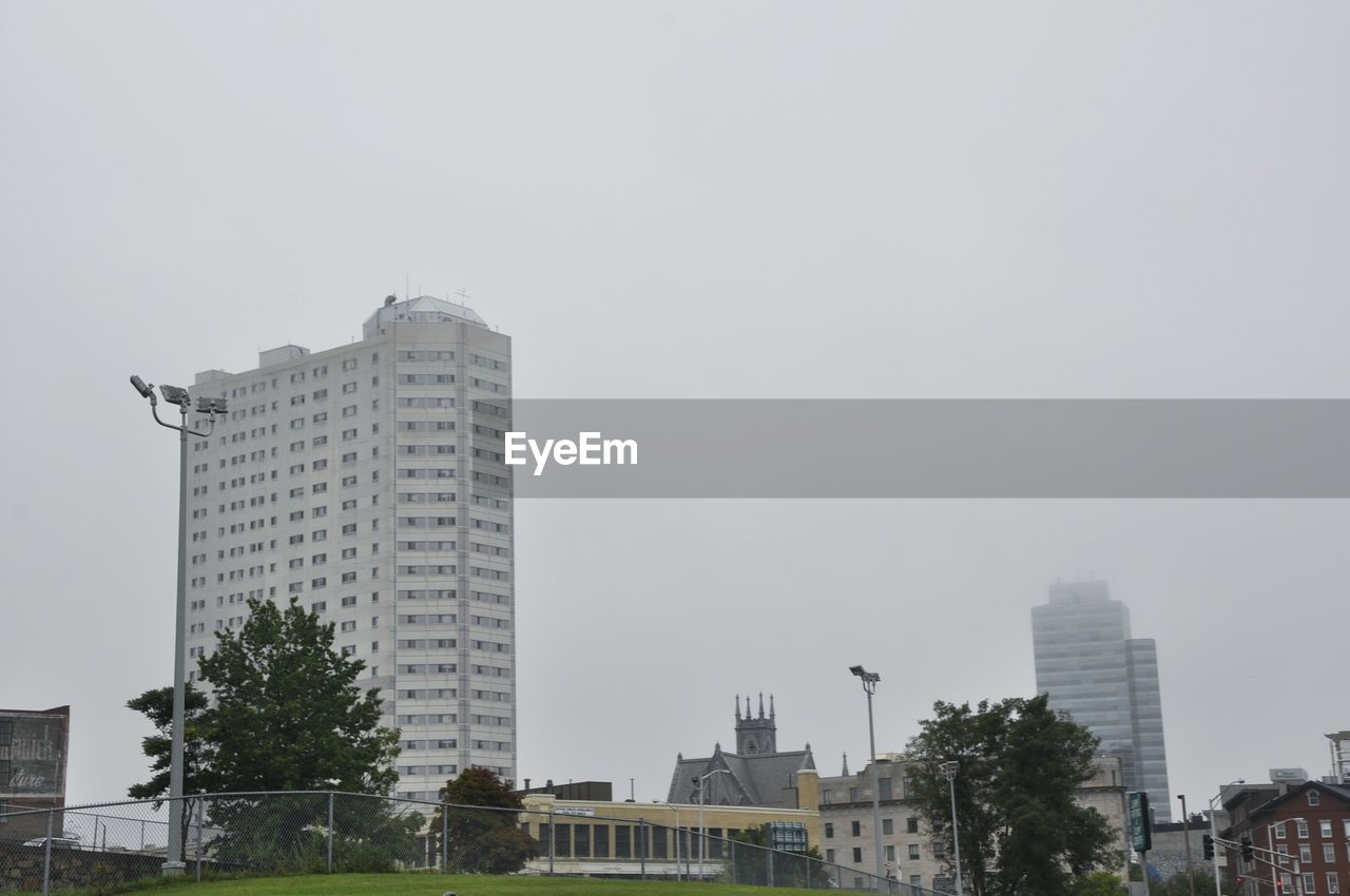 architecture, building exterior, city, skyscraper, built structure, tree, no people, modern, low angle view, outdoors, day, cityscape, urban skyline, sky